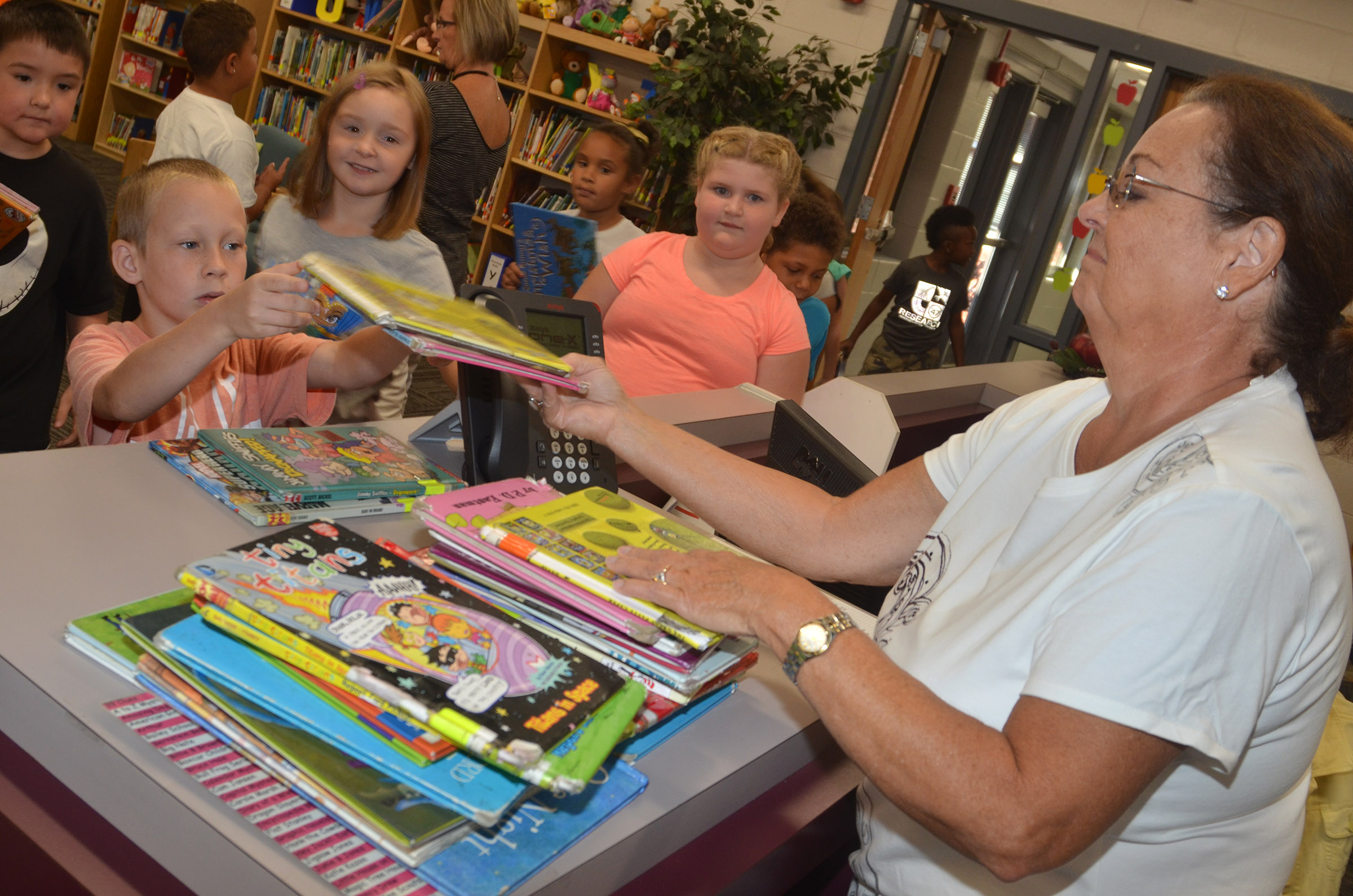 CES library assistant Lois Kemp helps second-graders check out books.