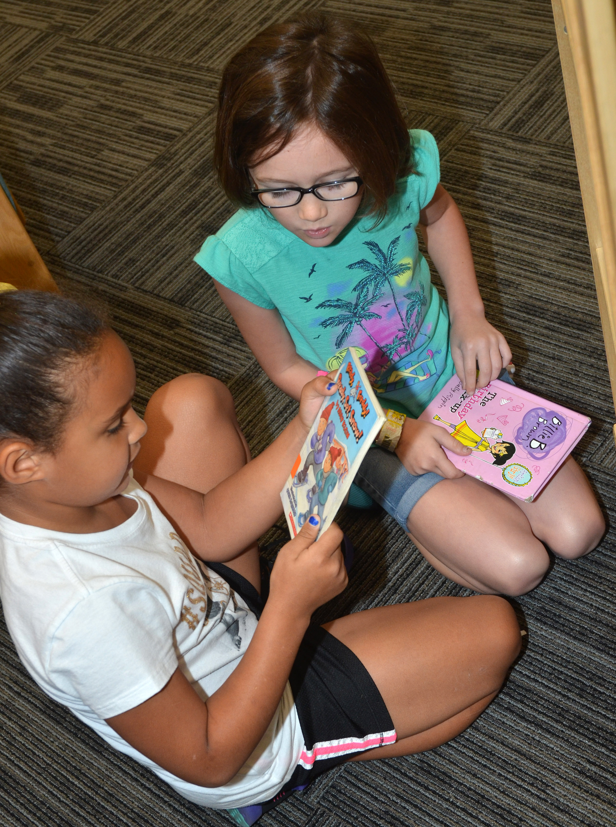 CES second-graders Amani Bridgewater, at left, and Anna Keith look at books in the library.