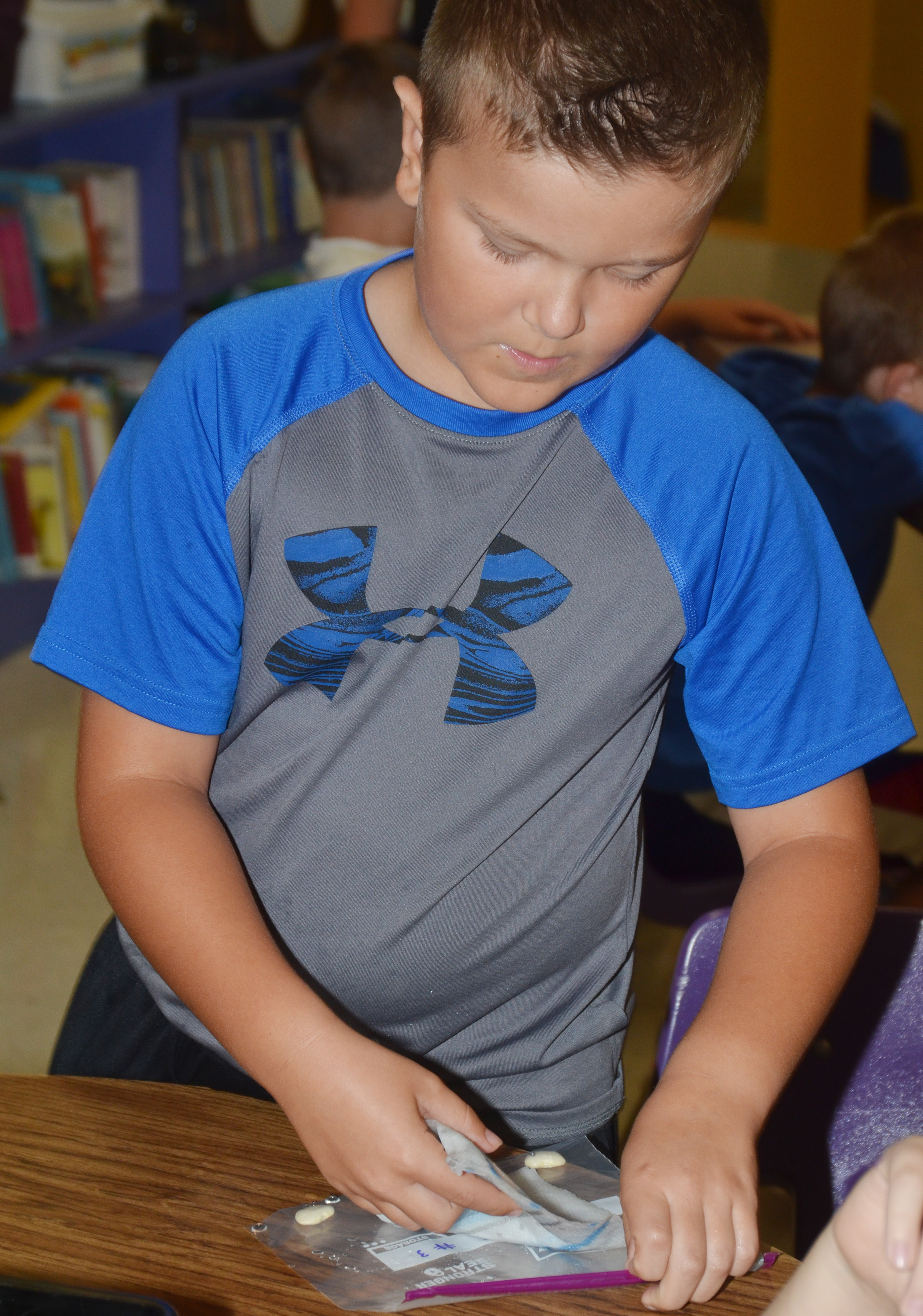 CES third-grader Cayton Lawhorn places his group's lima bean inside a wet paper towel and then inside a Ziploc bag.