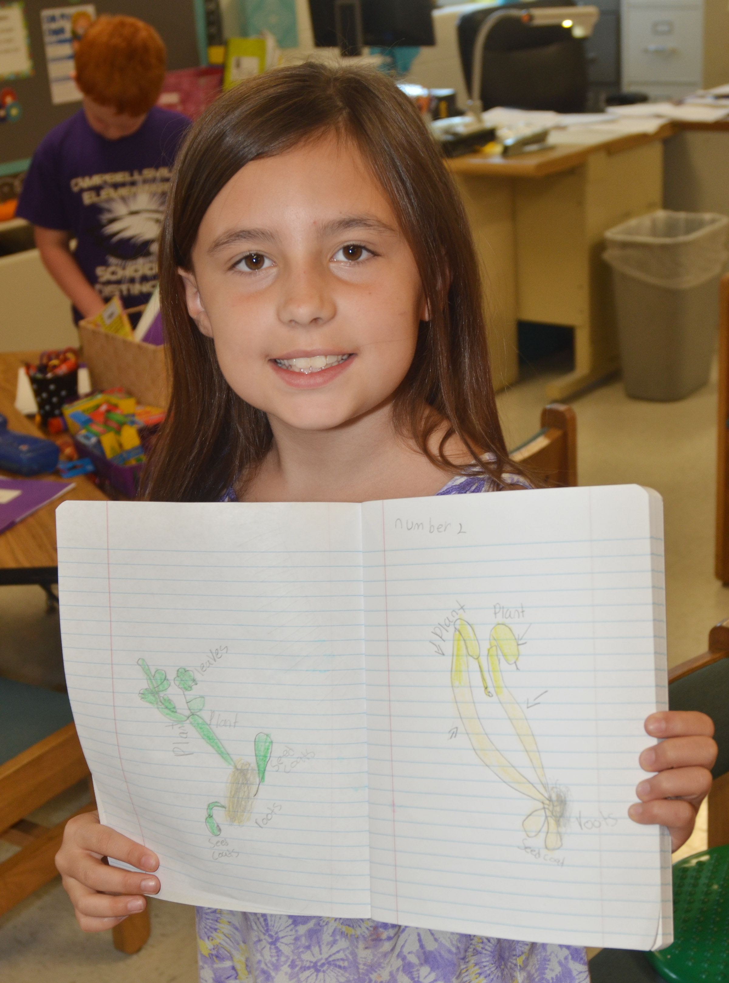 CES third-grader Annabelle Brockman holds her journal, in which she recorded her lima bean's progress.
