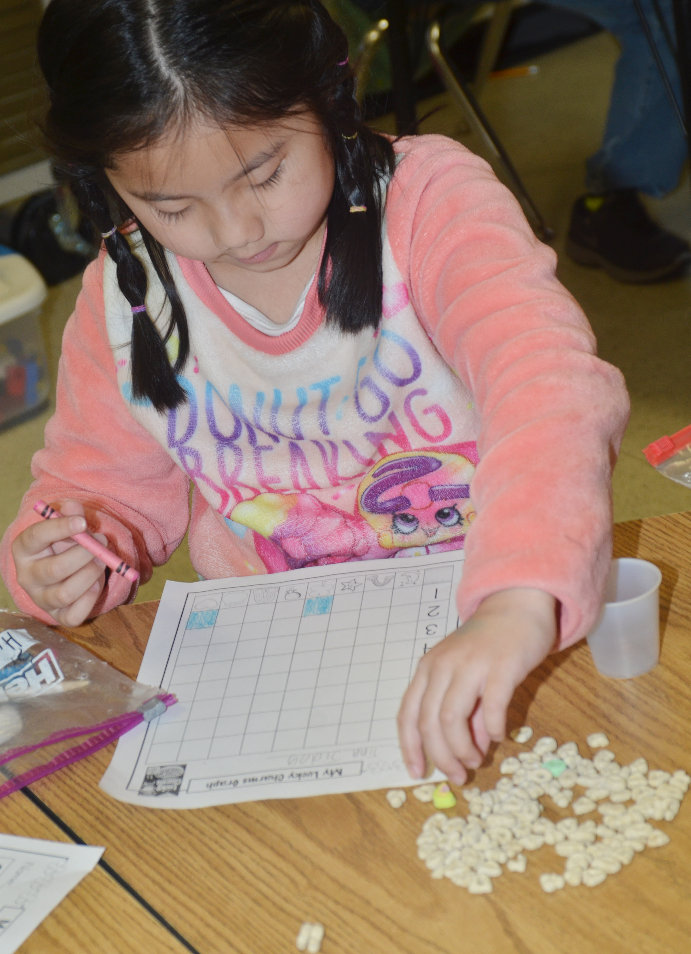 CES first-grader Tina Jiang sorts her Lucky Charms marshmallows.