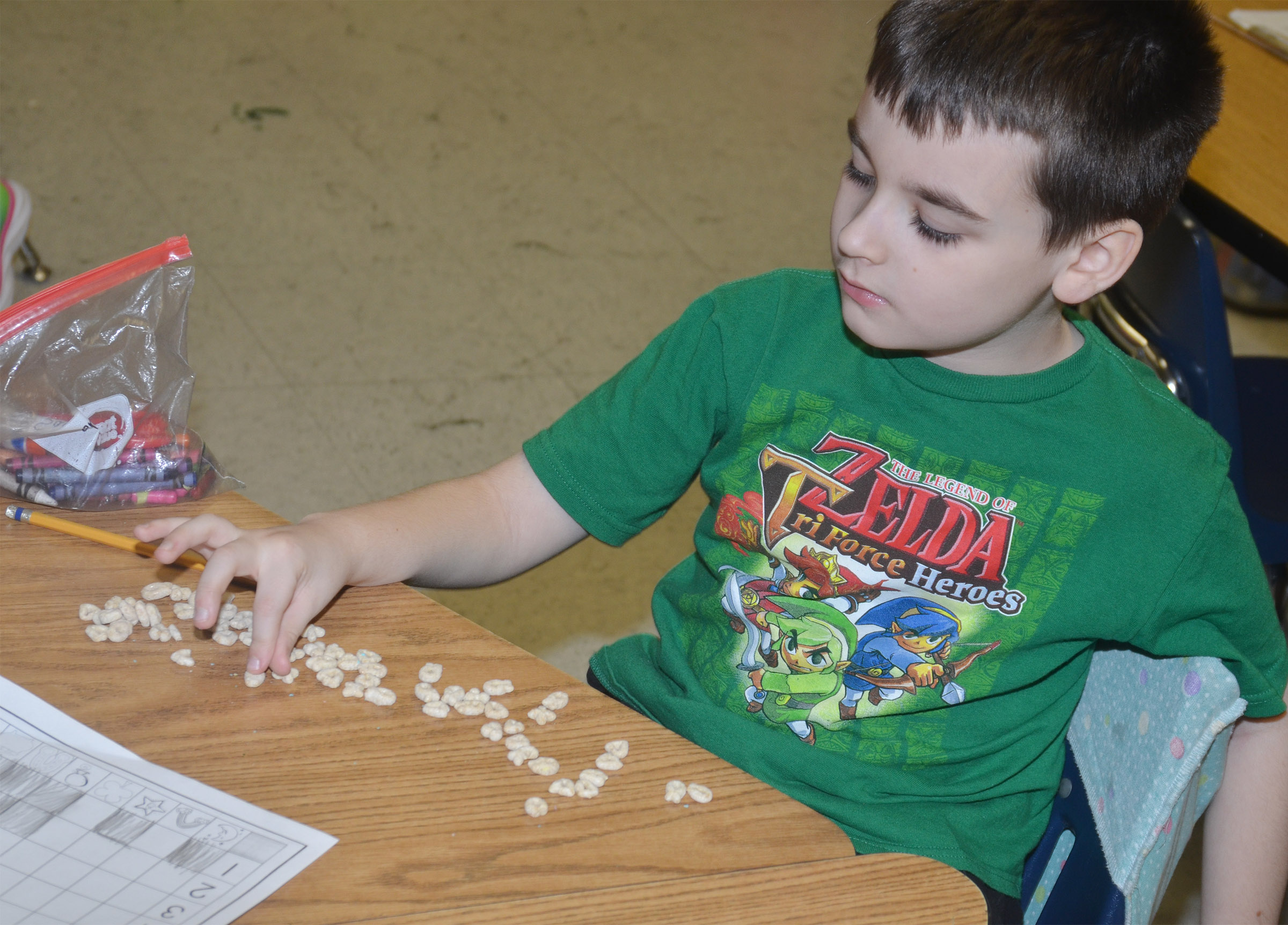 CES first-grader Sawyer Lange counts his cereal pieces.