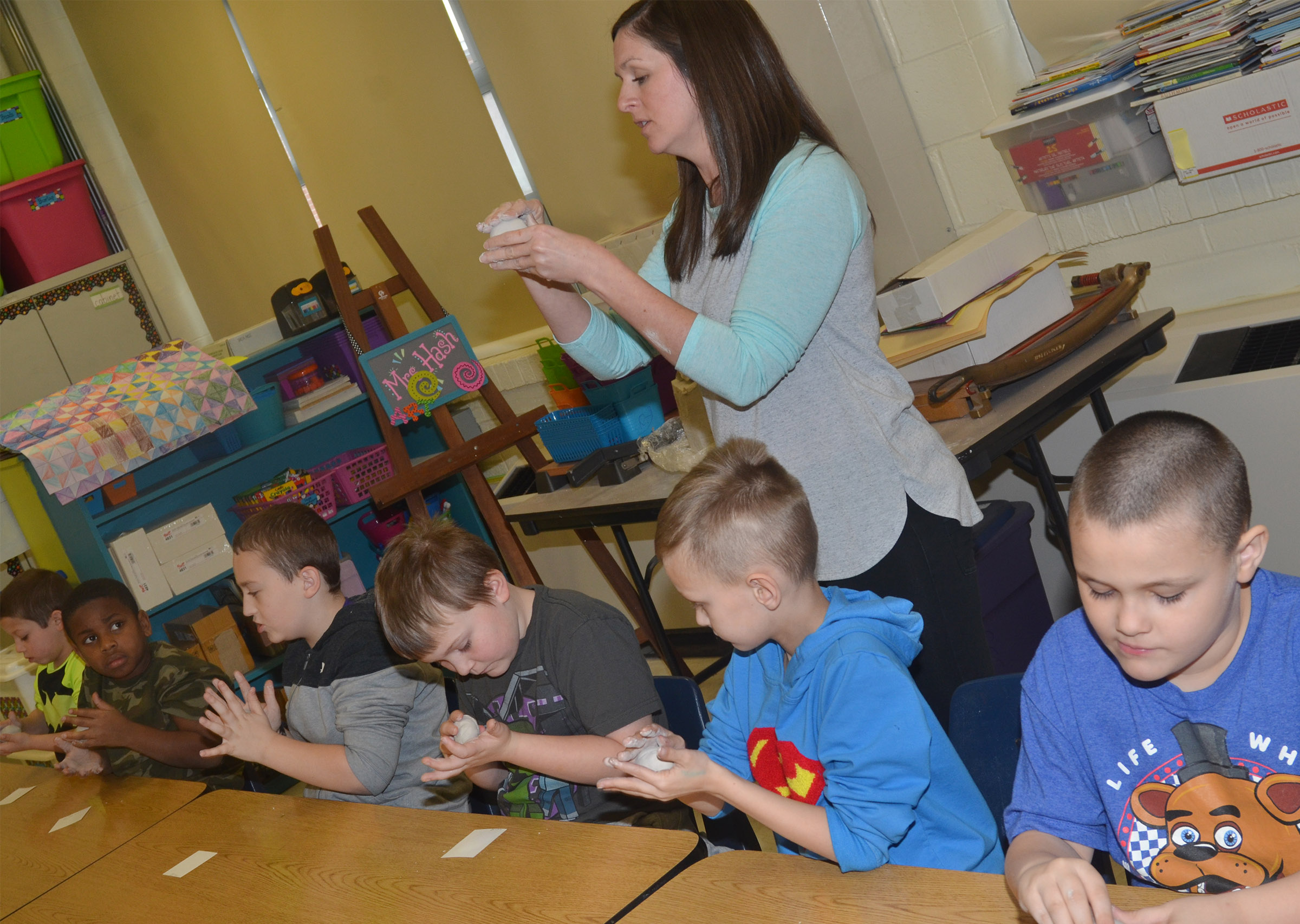 CES art teacher Adrienne Hash teaches second-grade students in Melanie Cox's class how to make pinch pots.
