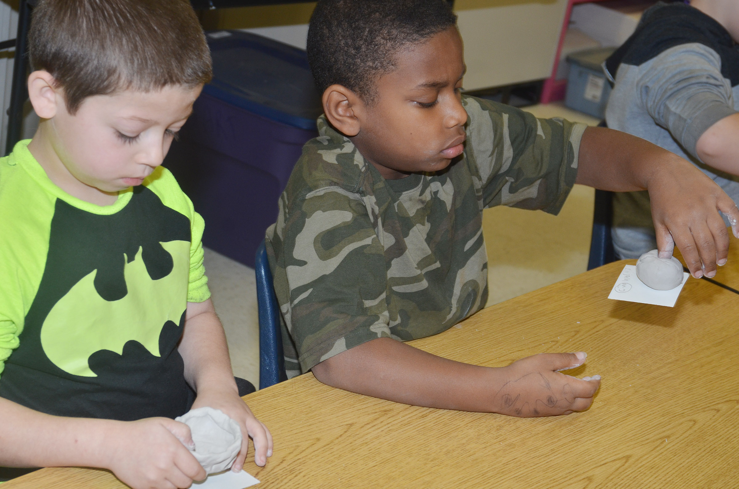 CES second-graders Dre Gurley, at left, and Elijah Spurling use their hands to shape their clay into pots.