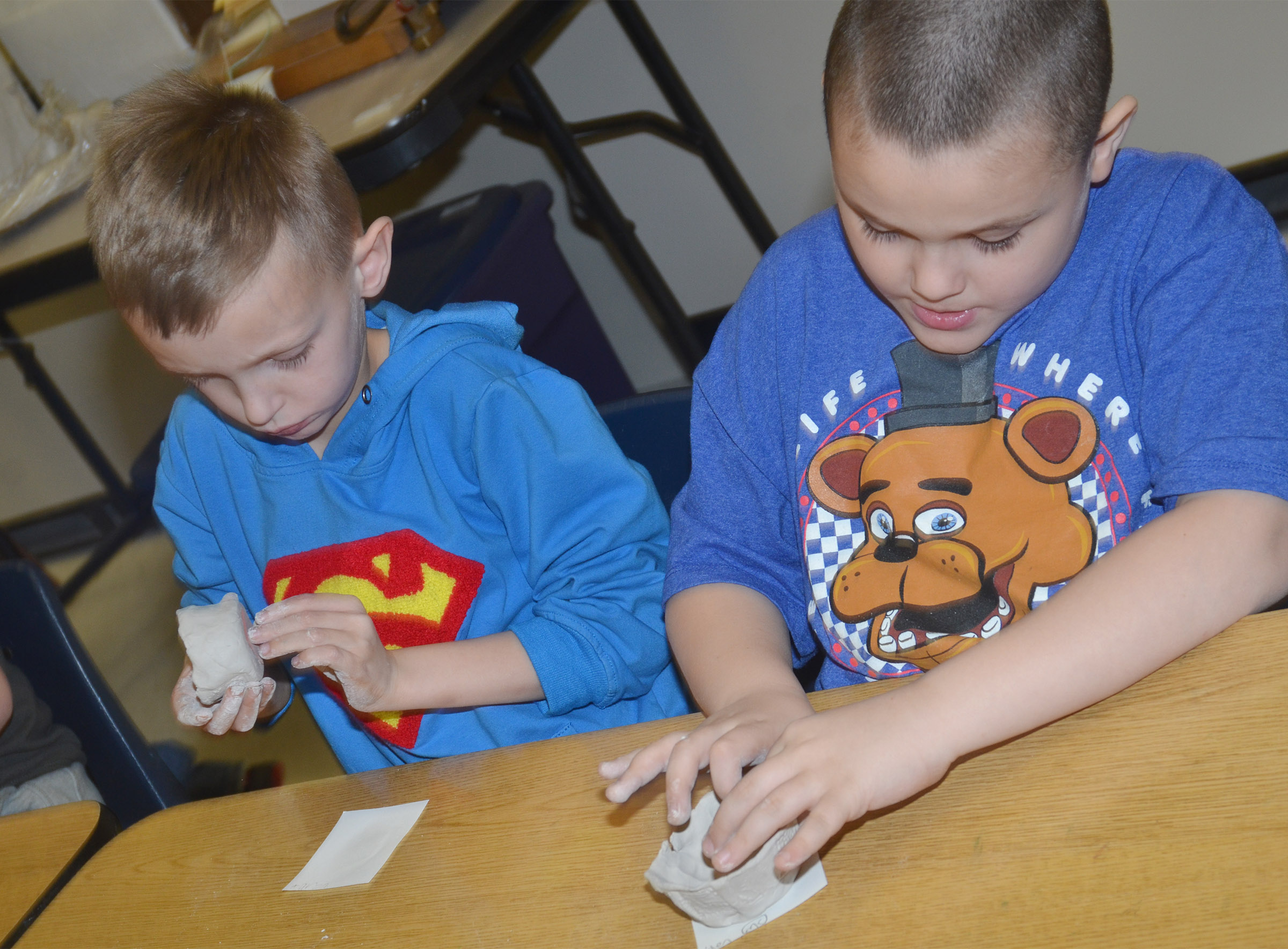 CES second-graders Aaron Ritchie, at left, and Aiden Dziabula shape their pots.