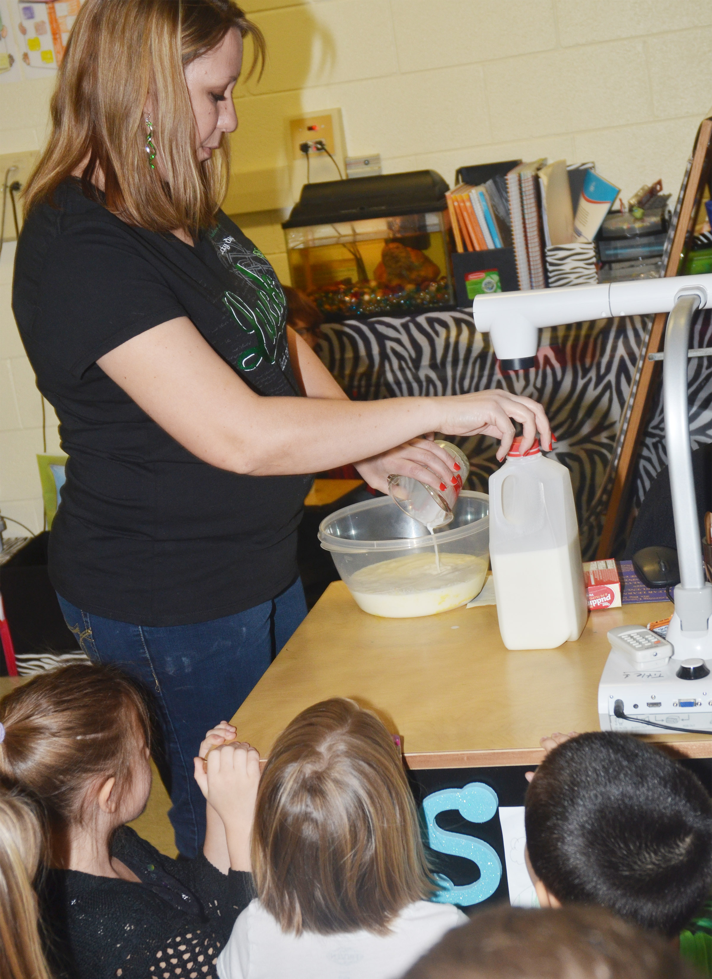 CES first-grade teacher Amanda Greer adds milk to her class's vanilla pudding mix, which eventually turned green.