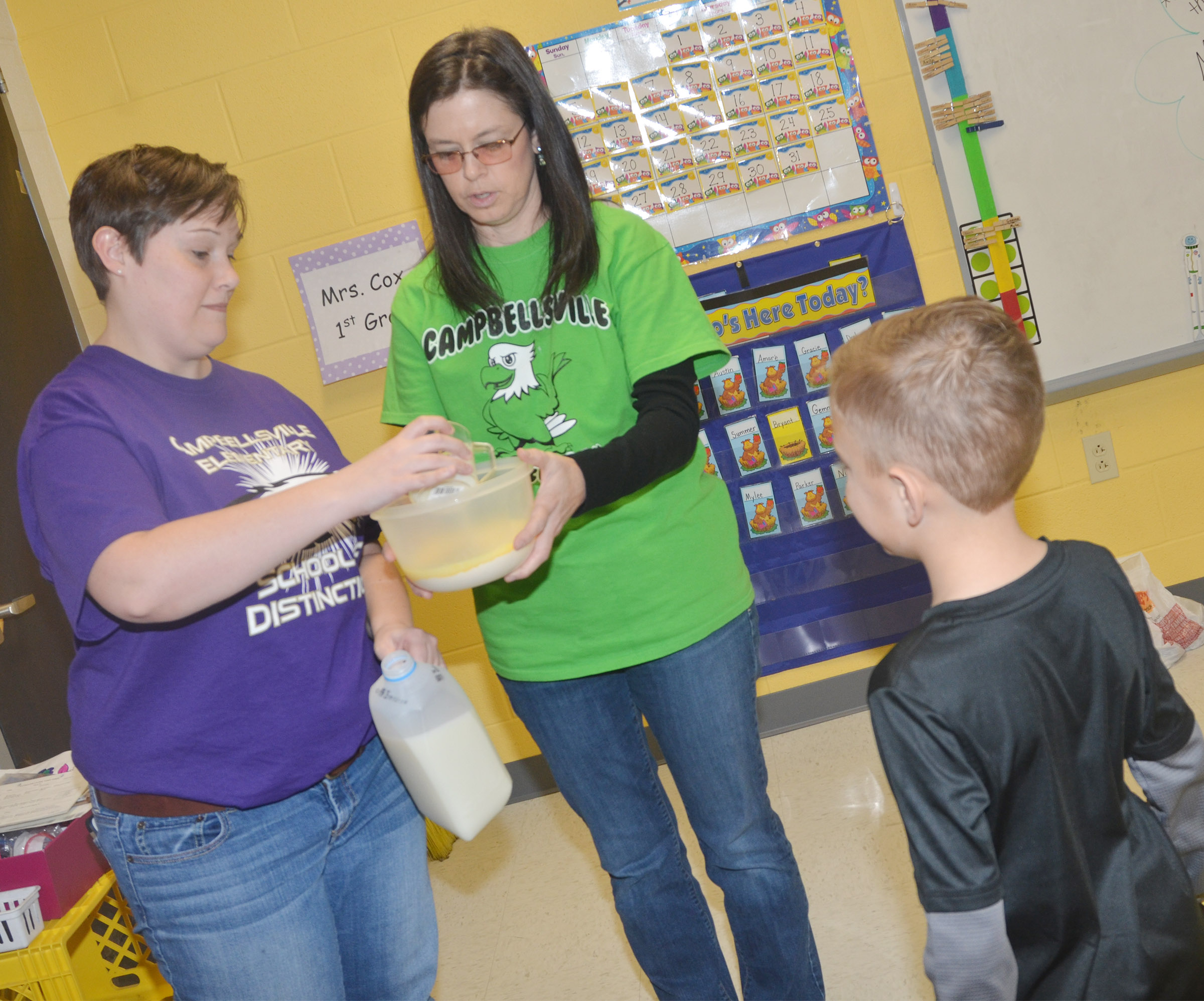 CES Wings Express Director Amanda Barnett, at left, and first-grade teacher Shirley Cox add milk to their pudding mix.