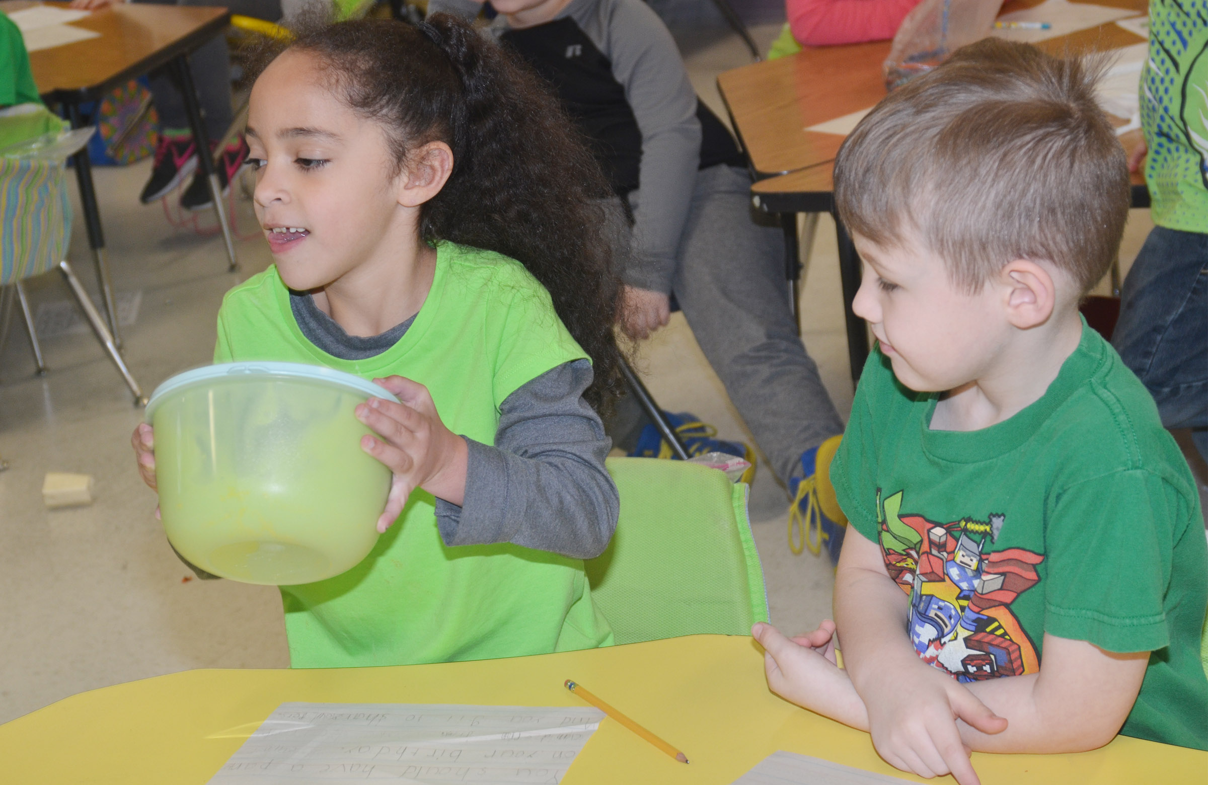 CES first-graders Essence Hunter, at left, shakes the pudding mixture as Lucian Abel waits his turn.
