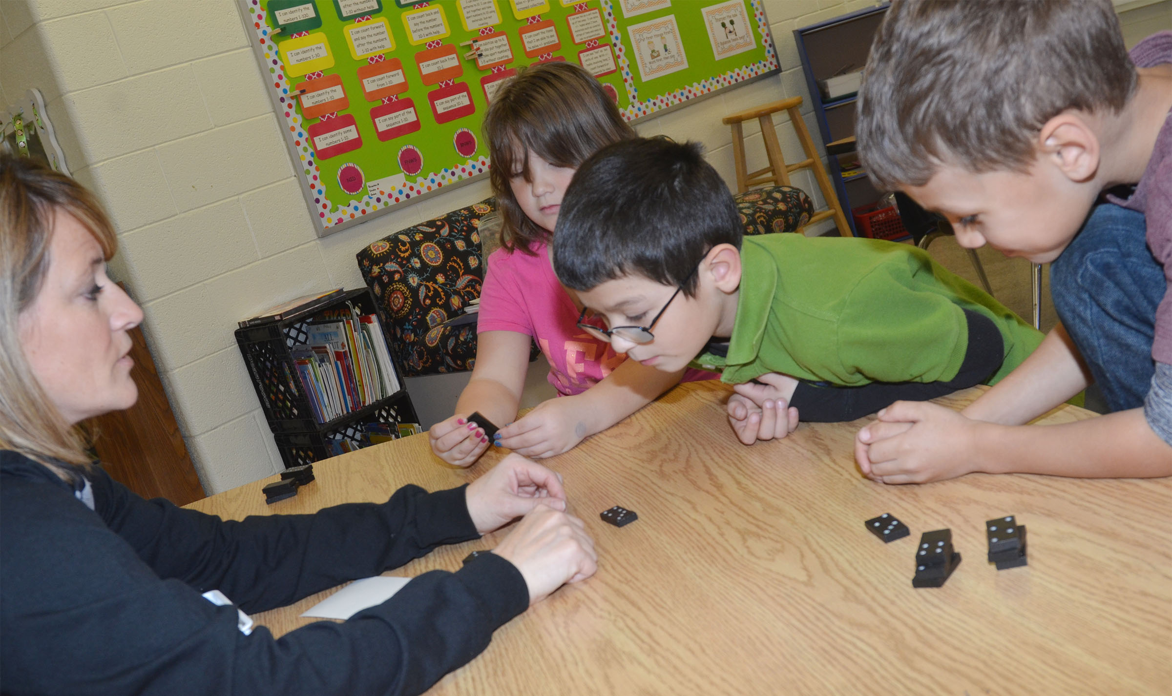 CES math interventionist Vanessa Adkins plays a Dominos game with, from left, first-graders Destiny Rhinehart, Henry Martinez and Shylan Dunn.