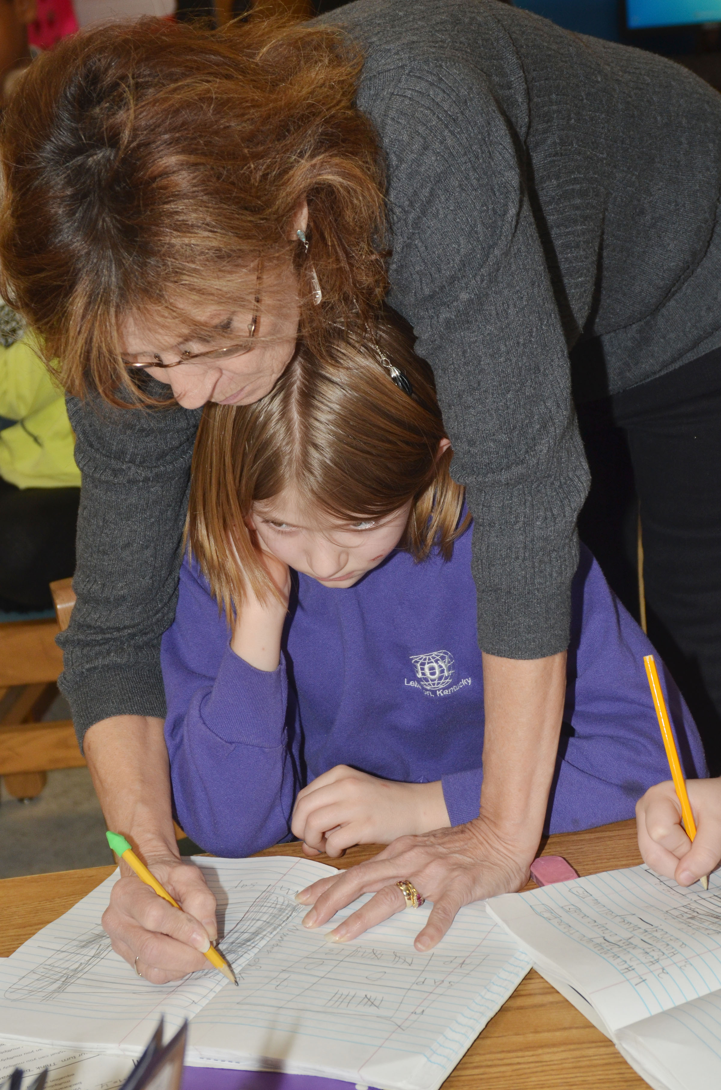 CES third-grade teacher Marcia Sharp helps student Kelsi Shuck make her bar graph.