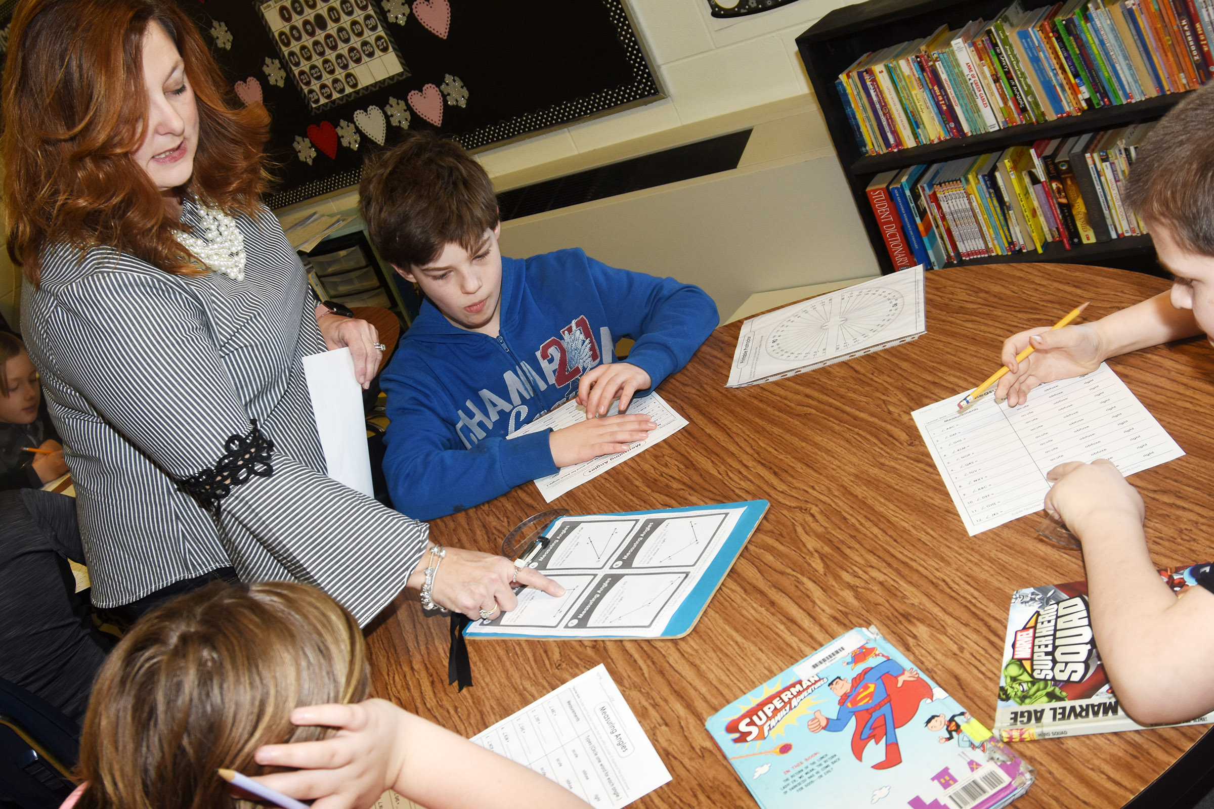 CES fourth-grade teacher Garnetta Murrell talks to her students about how to measure an angle. Pictured are, from left, Mary James, Joshua Weise and Bobby Engle.