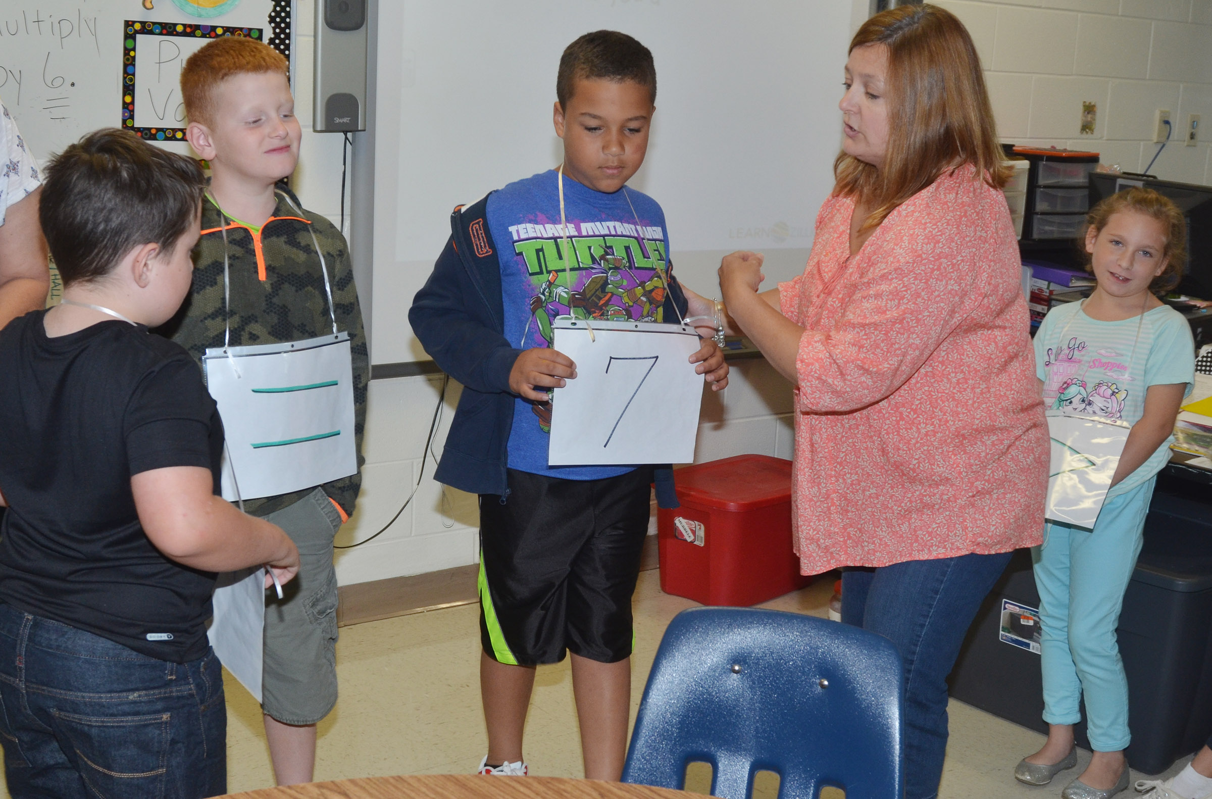 CES fourth-grade teacher Garnetta Murrell helps Westin Dudgeon, at left, Zarek Stone and their classmates determine which number is larger.