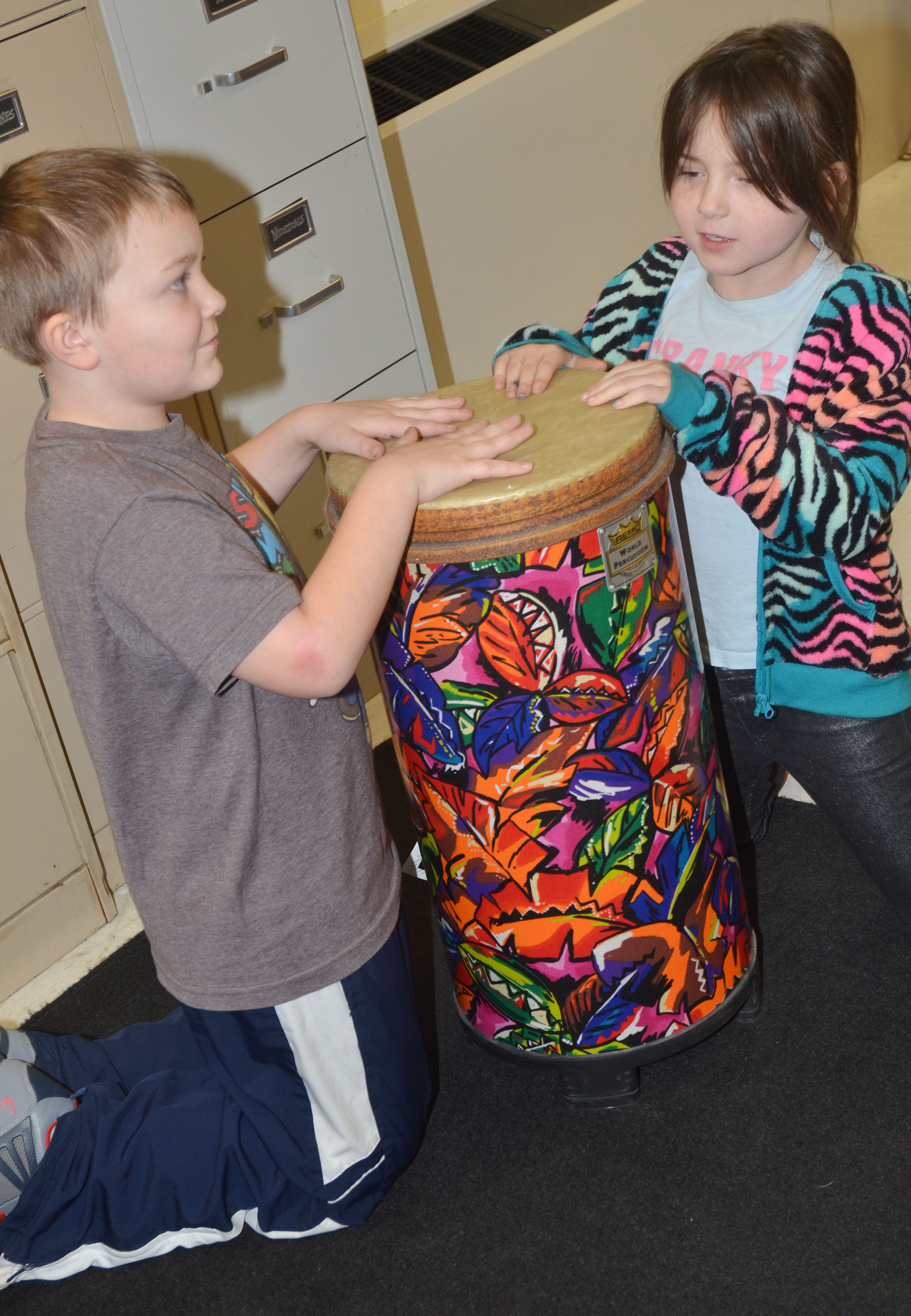 CES second-graders Griffin Skaggs, at left, and Kendall Cruz practice rhythms on the drums.