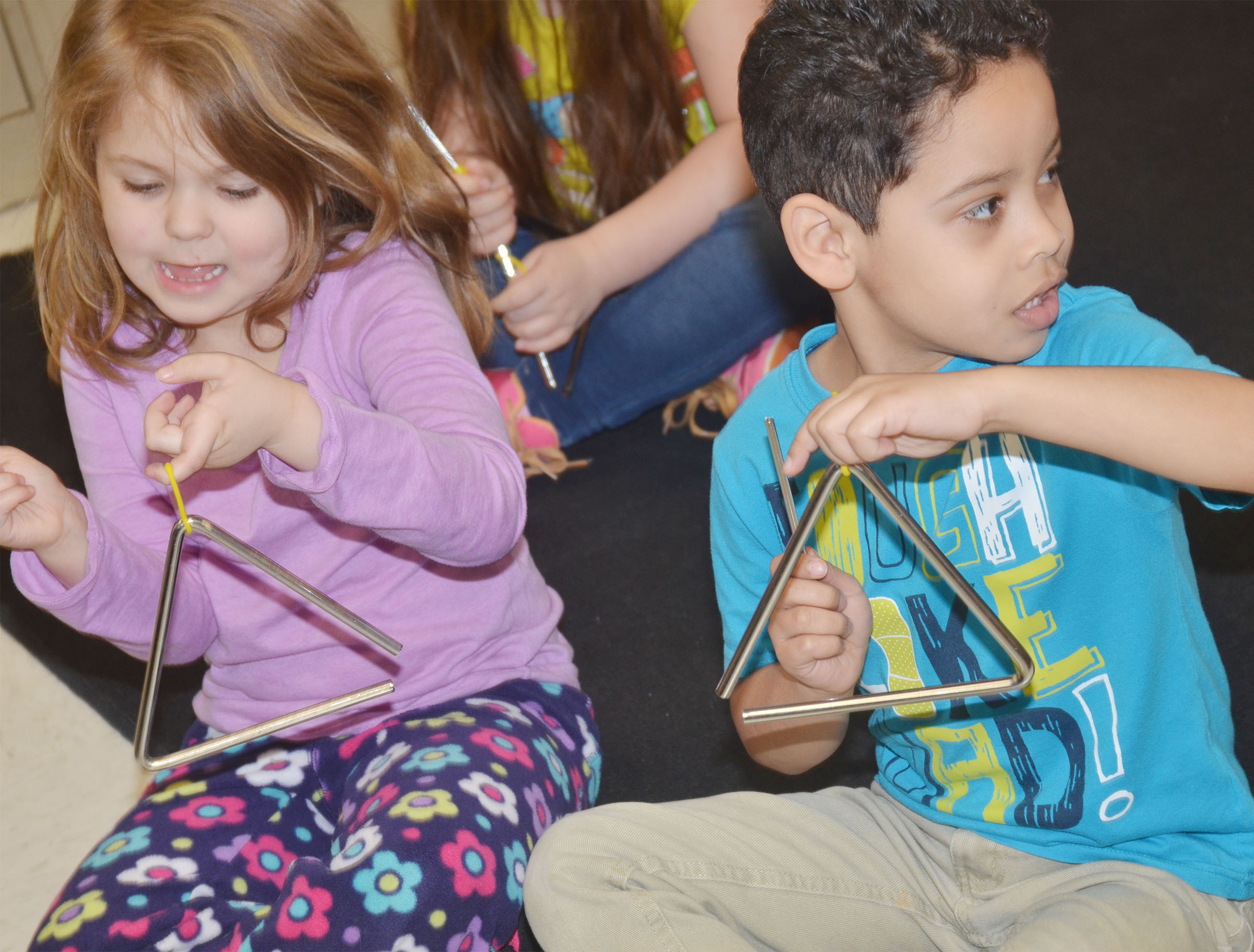 CES kindergarteners Aubrey Wilson, at left, and Demarcus Noyola play the triangle.