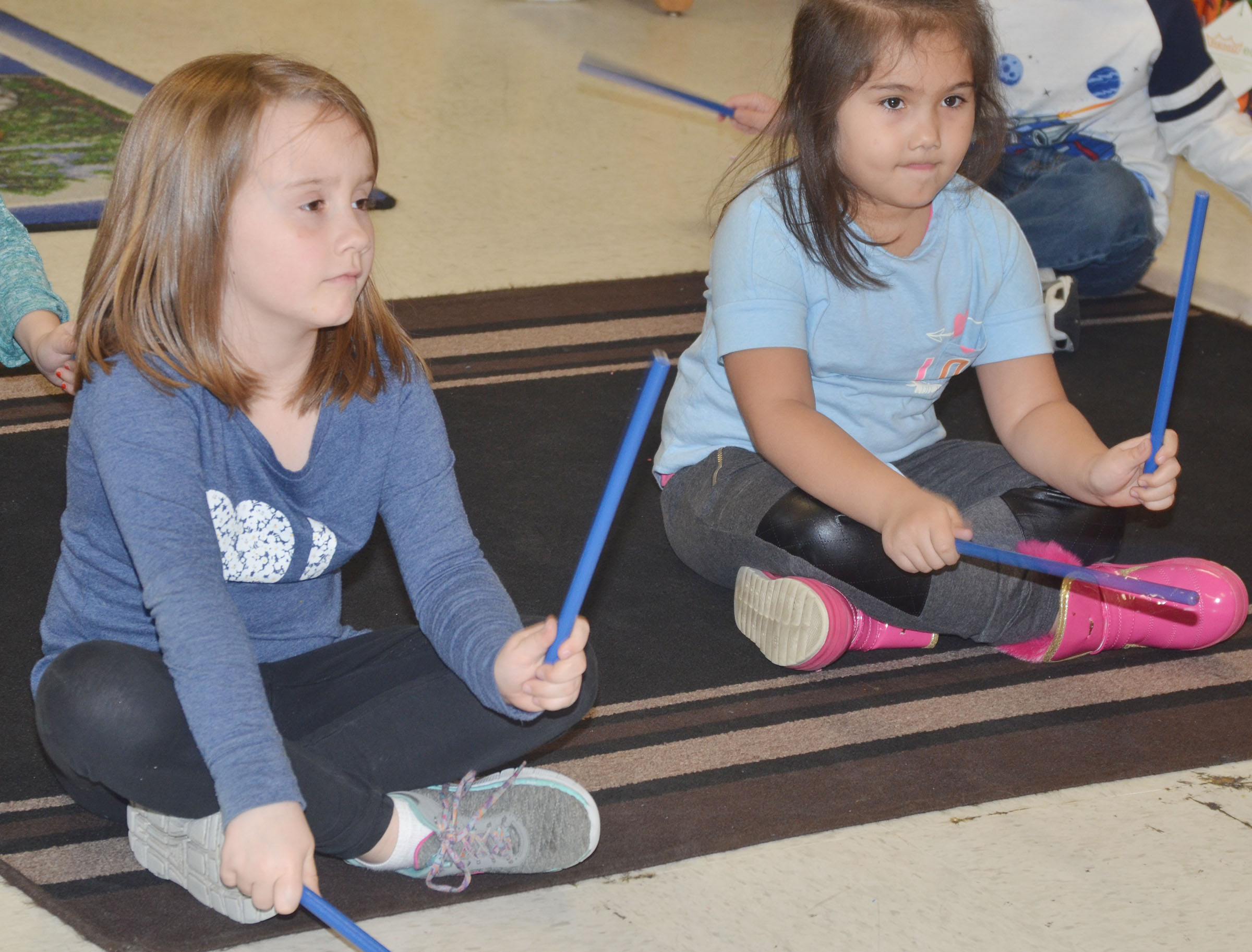 CES kindergarteners Natalee Shaw, at left, and Hannah Matias play the rhythm sticks.
