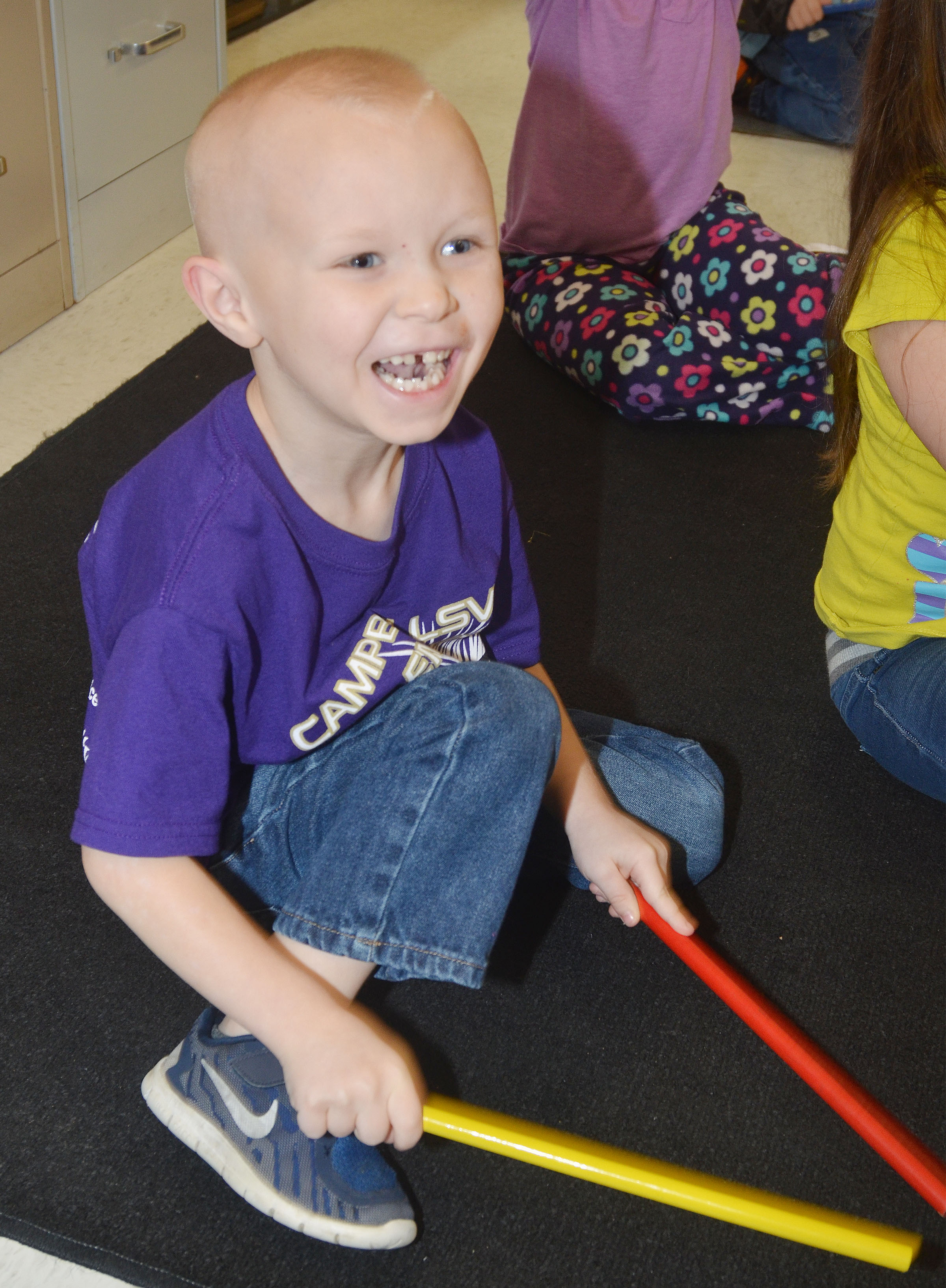 CES kindergartener Robert Atwood laughs as he plays the rhythm sticks.