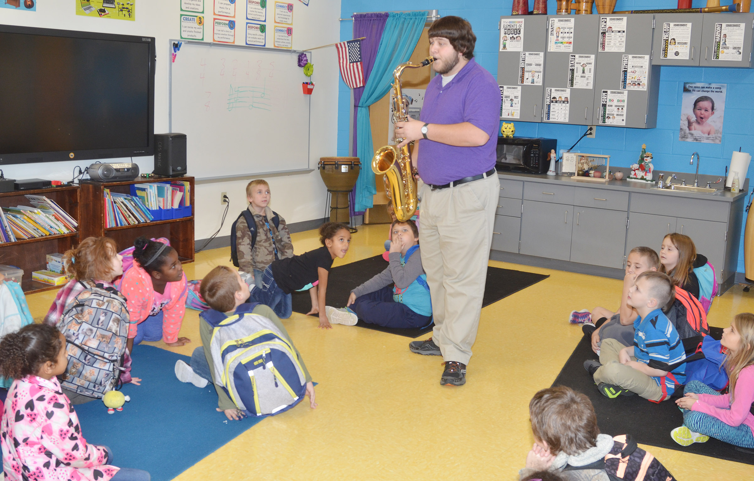 Campbellsville University education student Scott Caffee plays his tenor saxophone for CES first-graders.