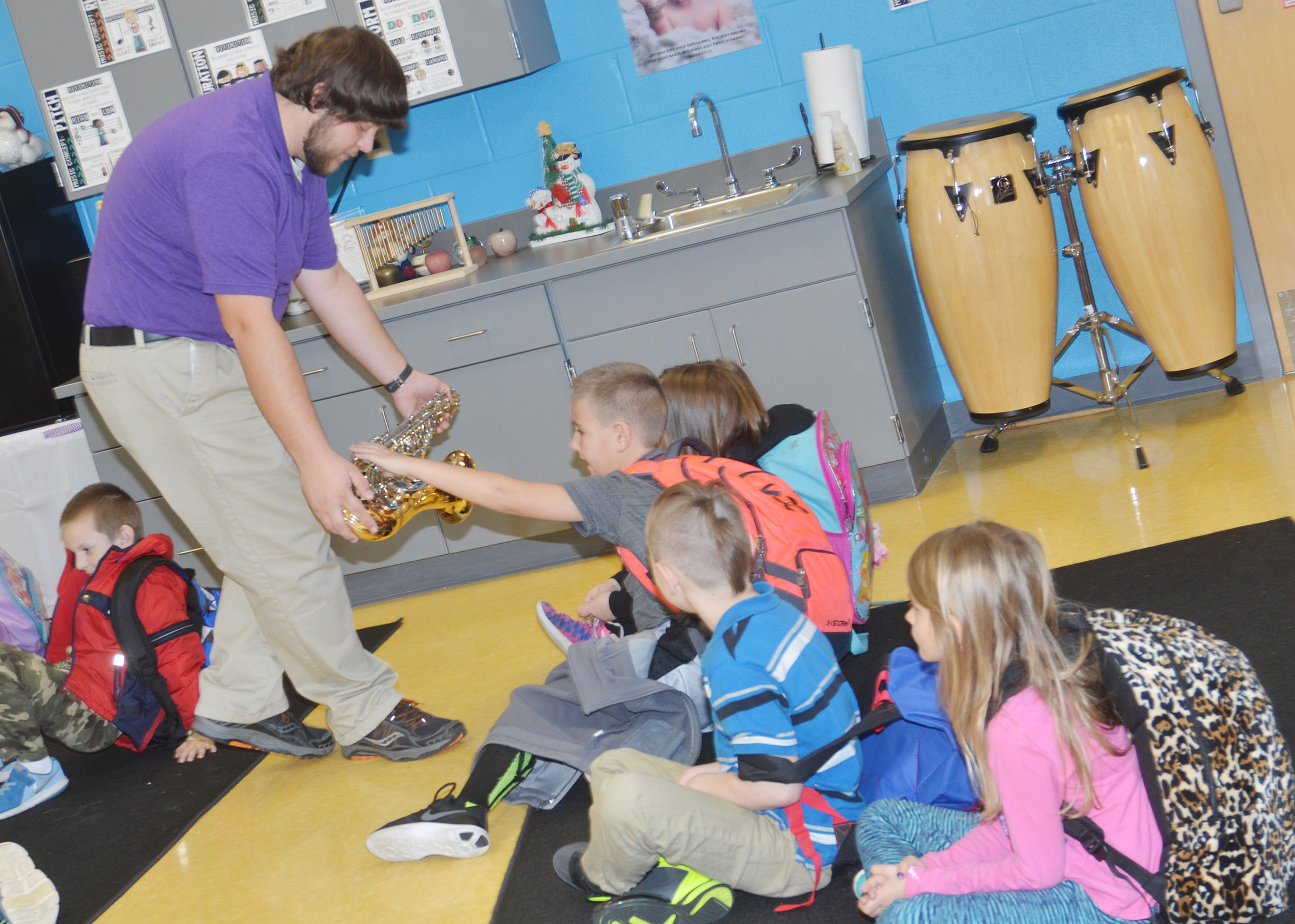 Campbellsville University education student Scott Caffee shows CES first-graders how pressing the keys on a tenor saxophone can change the note played.