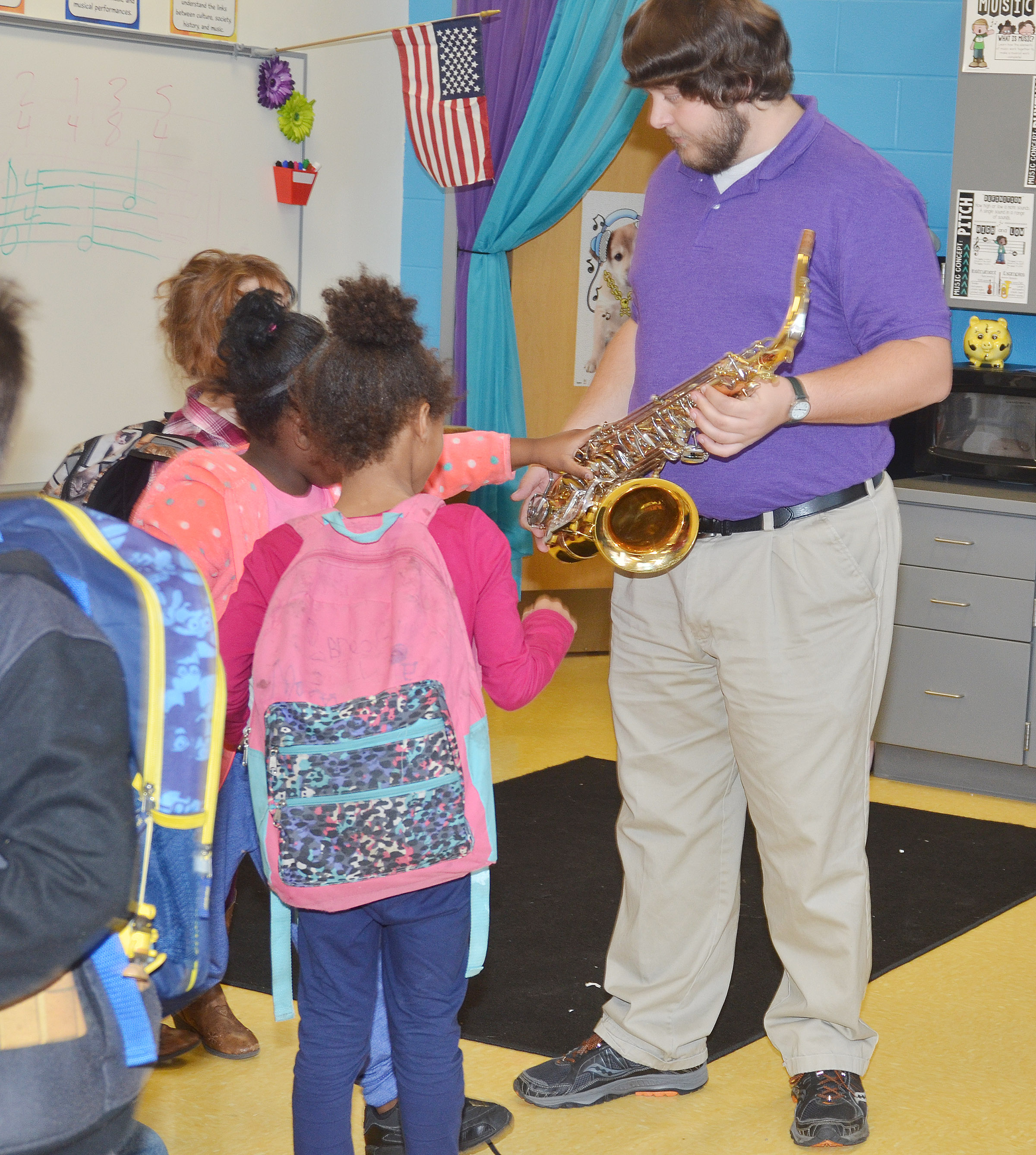 Campbellsville University education student Scott Caffee lets CES first-graders touch the keys on his tenor saxophone.