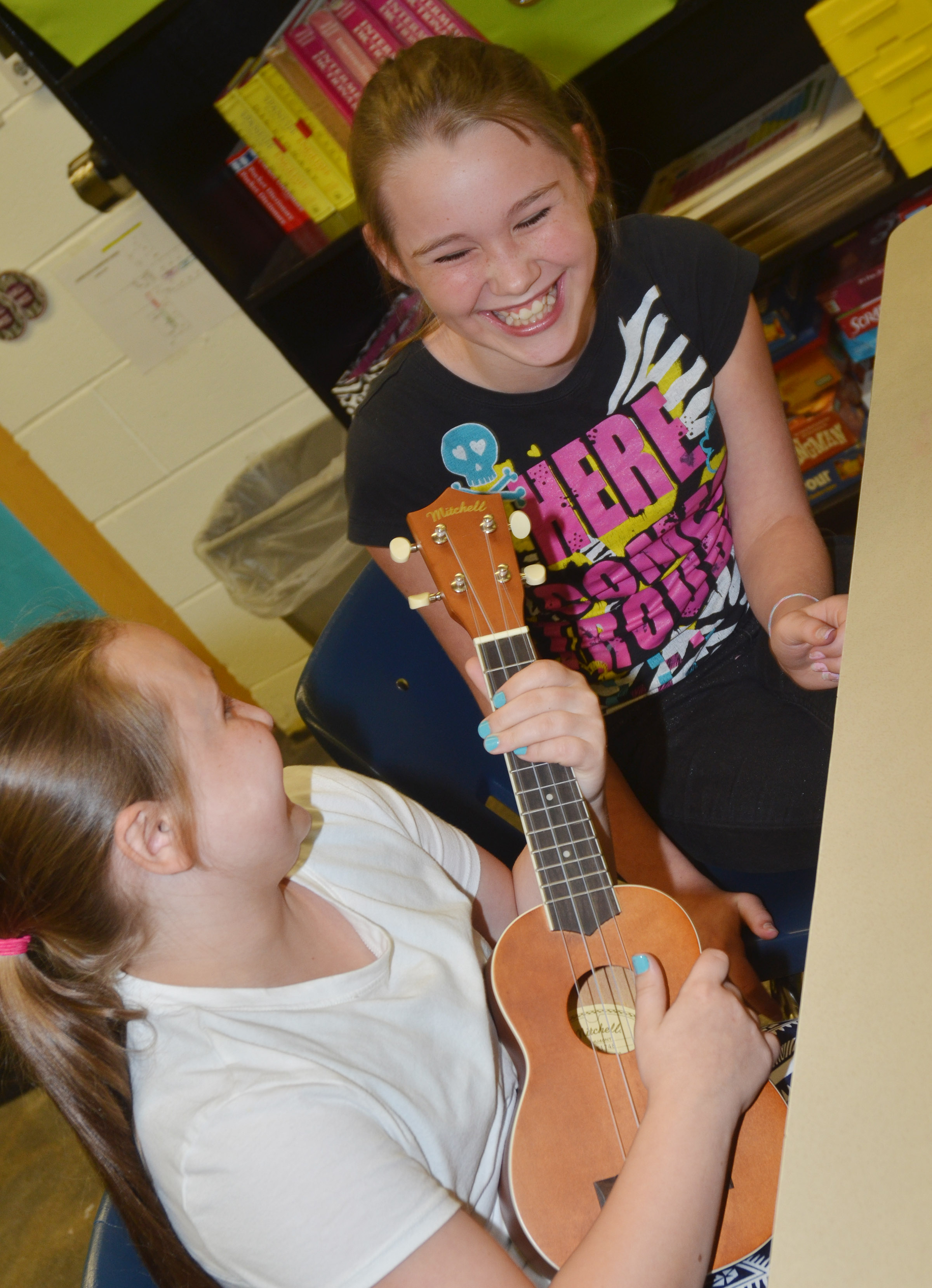 CES fifth-graders Shyanna Young, at left, and Brooklynn Giles laugh as they learn to play a chord.