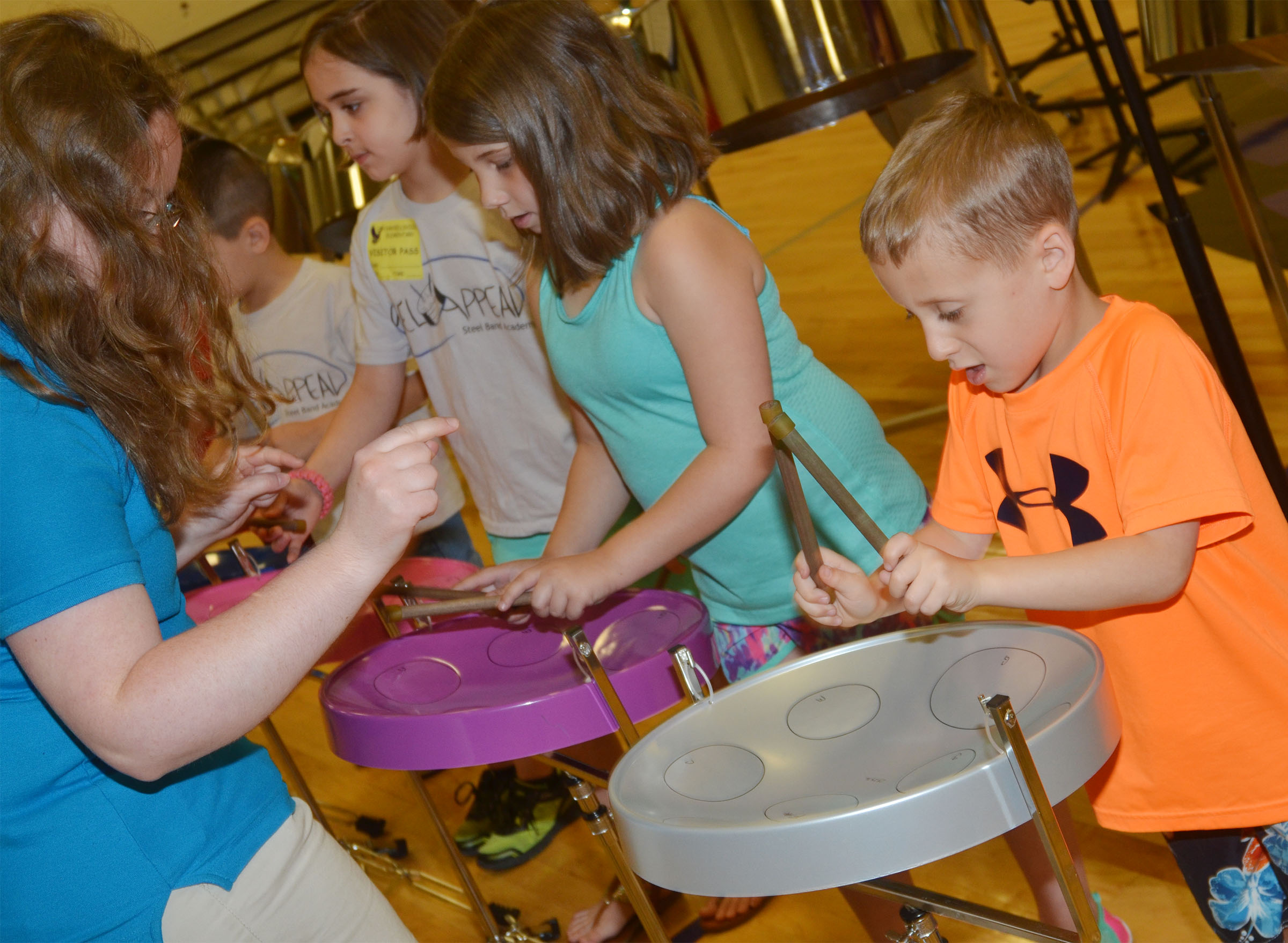 CES kindergartener Gavin Paris, at right, plays the steel drum with help from CU Steel Band member Kayla Ferguson.