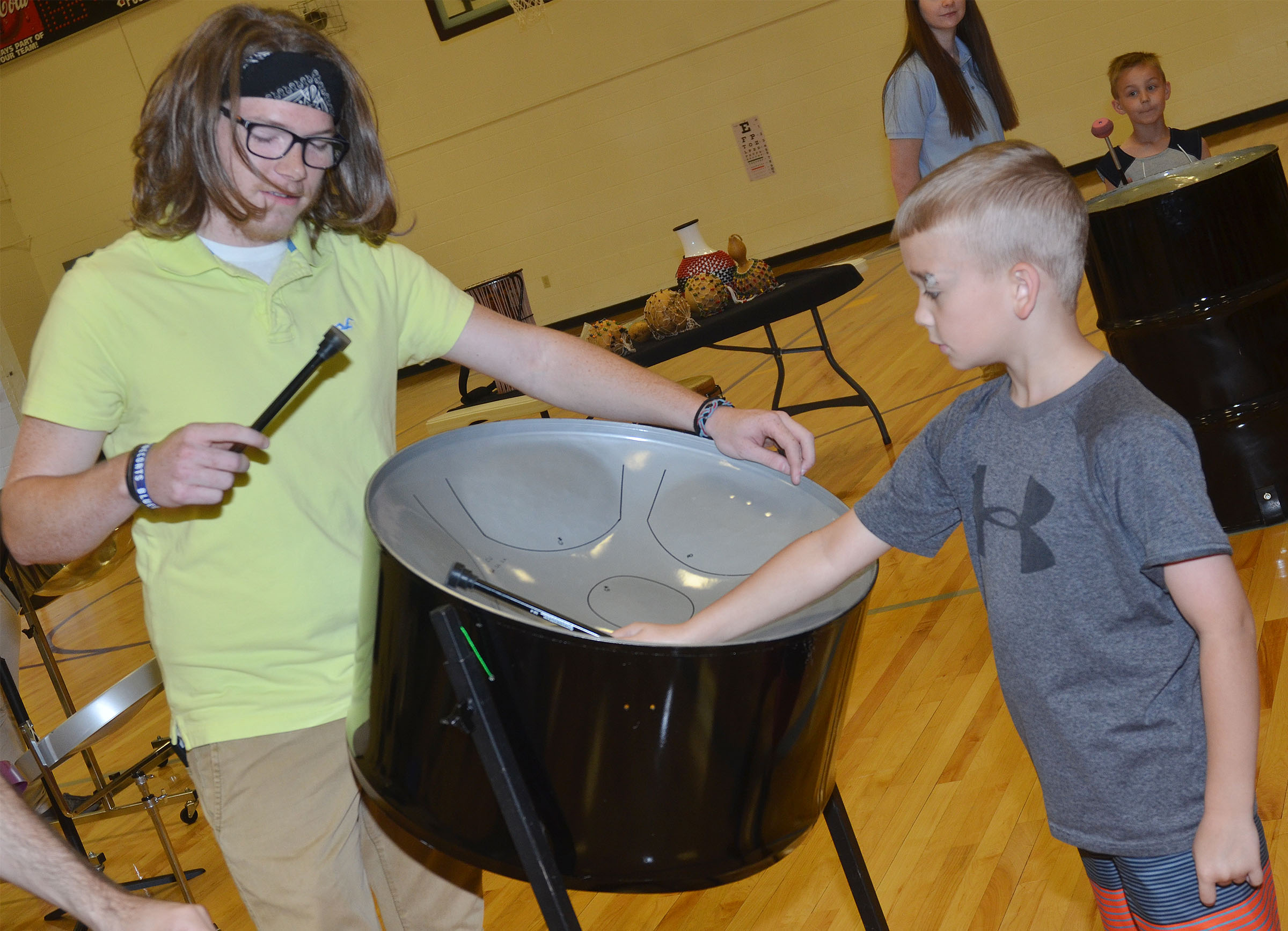 CES third-grader Cameron Estes plays the steel drum, with help from CU Steel Band member Joseph Howard.