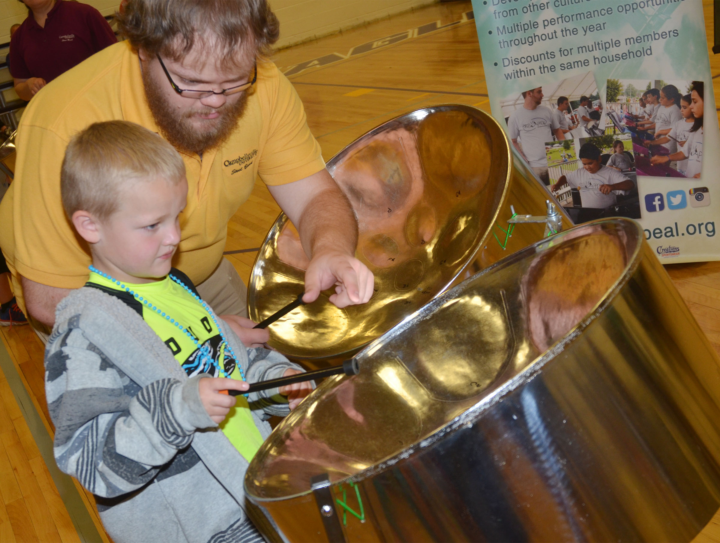 CES kindergartener Tristian Harris plays the steel drum, with help from CU Steel Band member Chris Blakley.