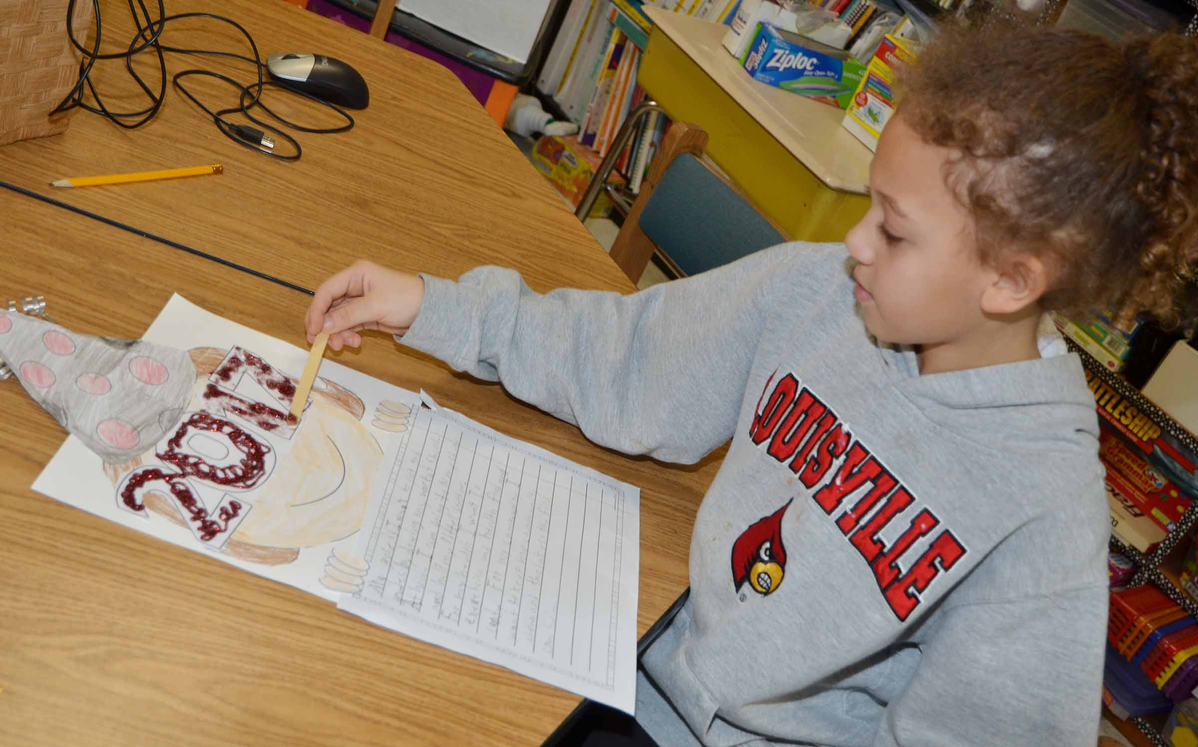 CES third-grader Alicia Spaulding adds glitter glue to her New Year's resolution.