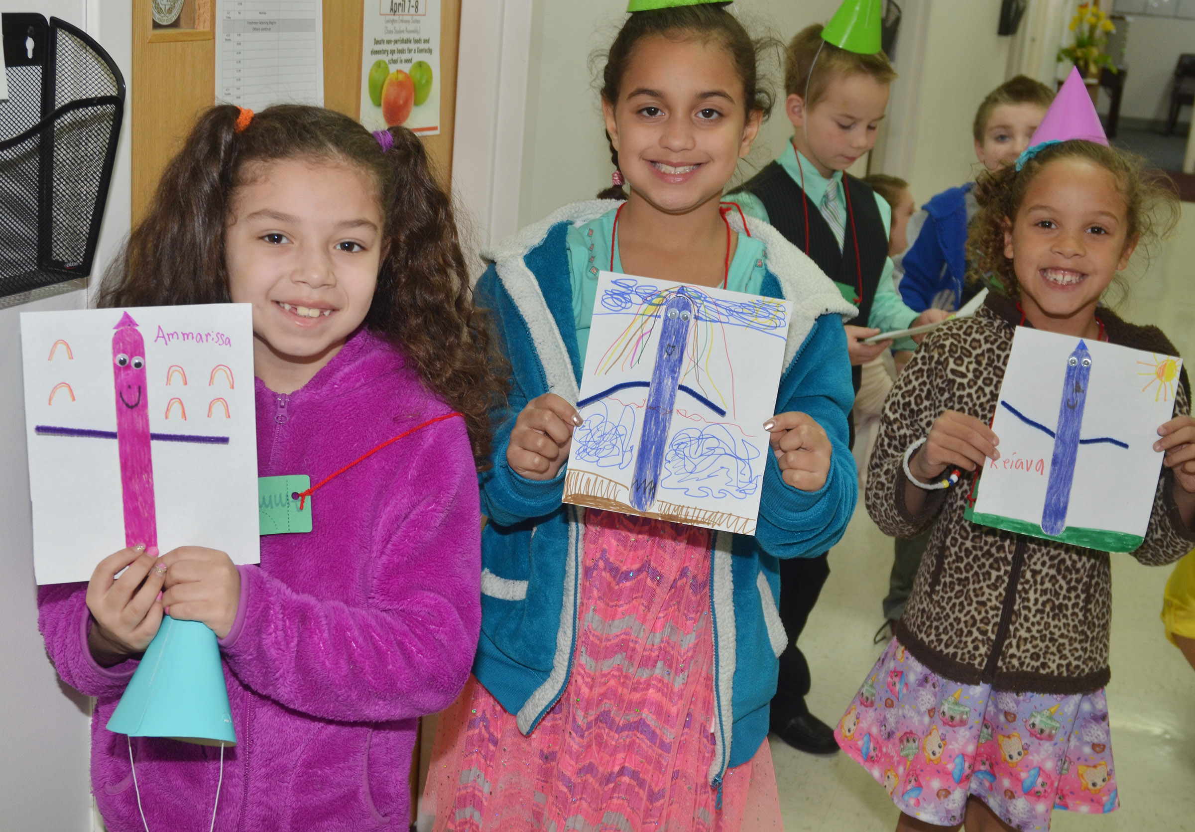 From left, CES first-graders Ammarissa Nunez, Maleigha Travis and Keiava Thompson hold their finished crayon people.
