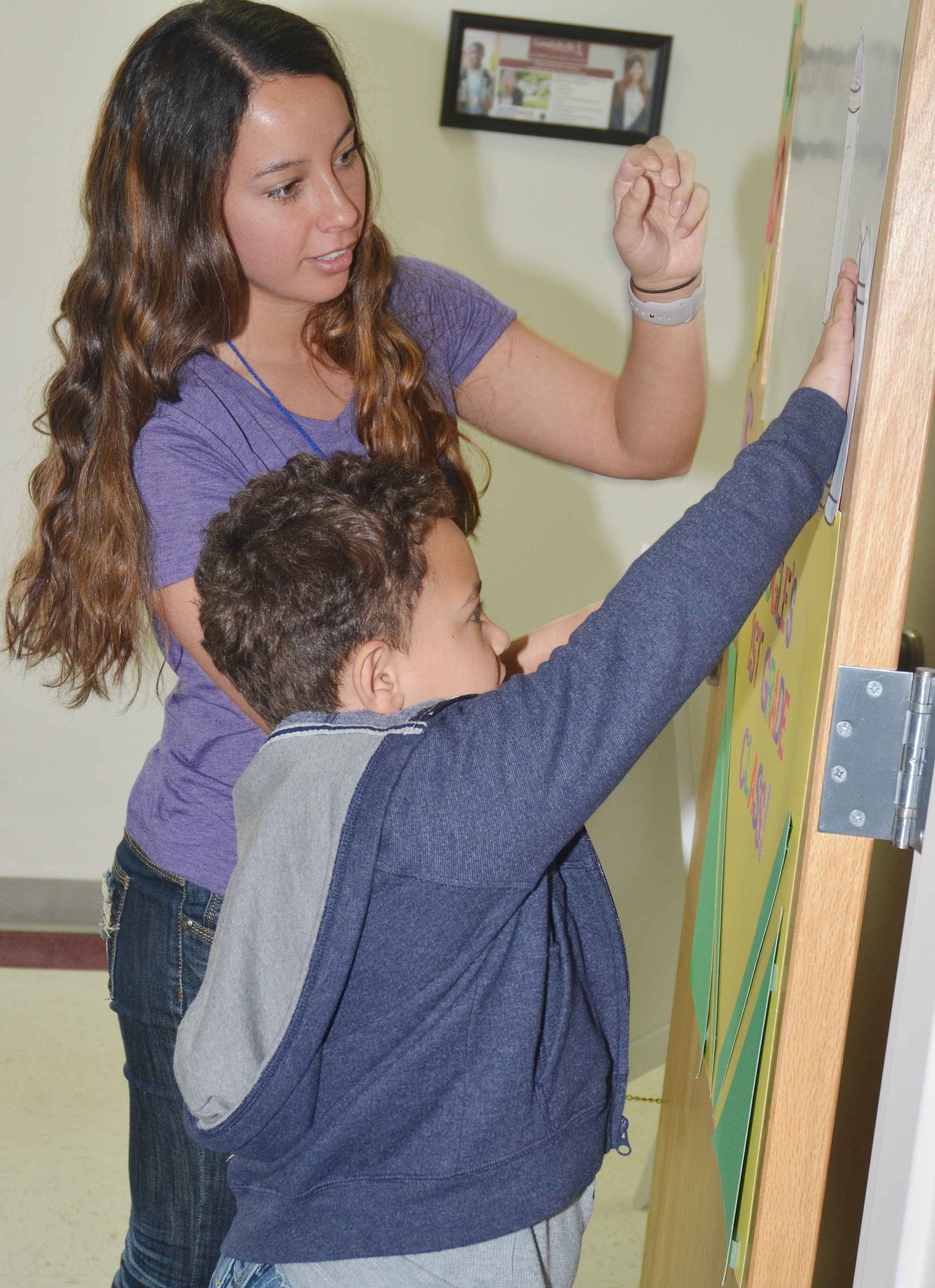 CES first-grader Marion Mann tapes the crayon he colored to the wall, beside the ones his classmates colored.