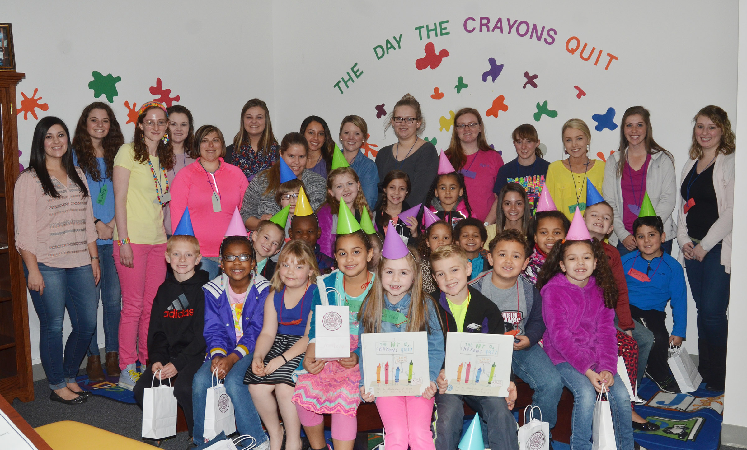 CES first-grade teacher Hailey Ogle, at left, and her students pose for a photo with CU education students.