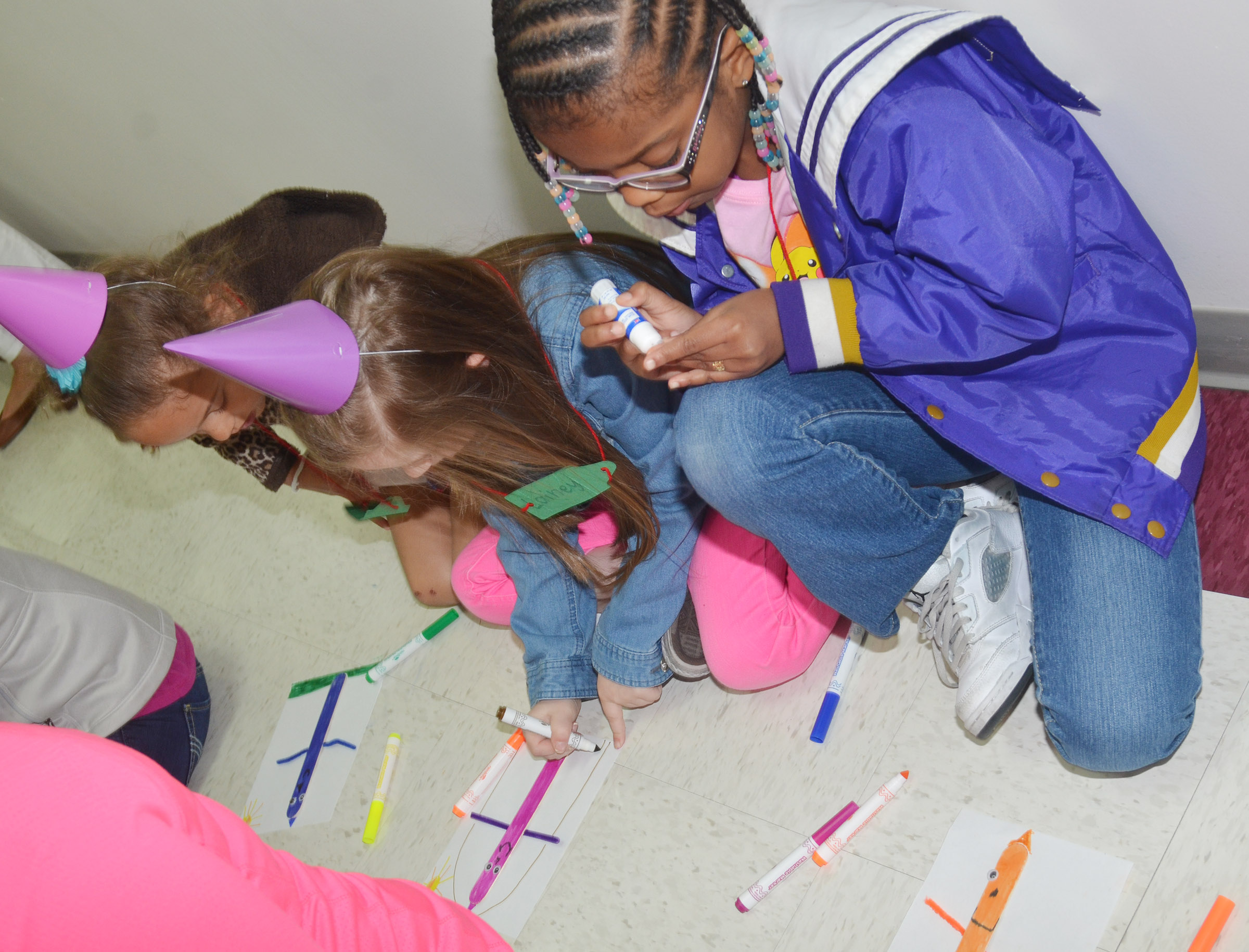 From left, CES first-graders Keiava Thompson, Lainey Price and Willow Griffin make their own crayon people.
