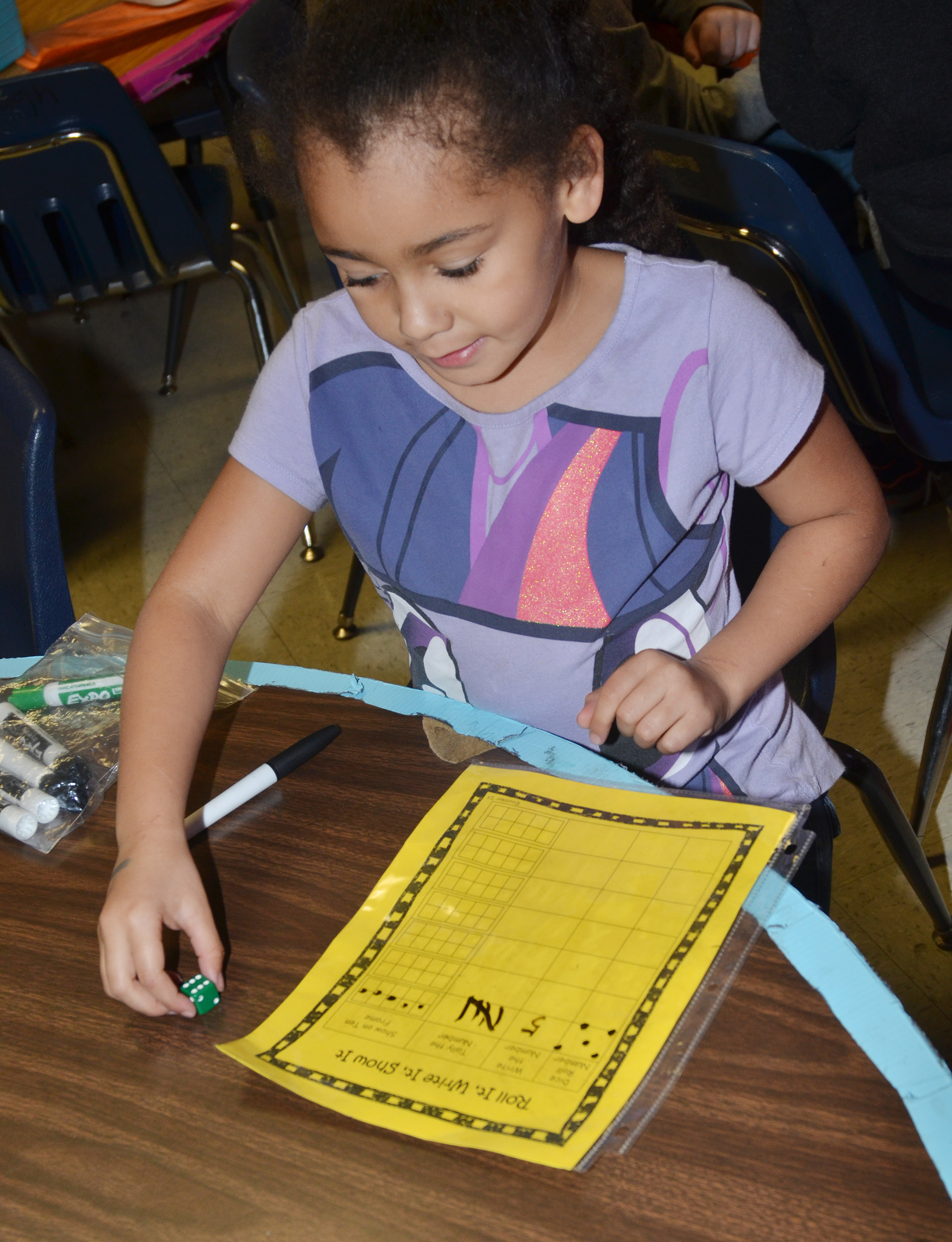 CES first-grader Keitona Whitehead plays a math dice game.