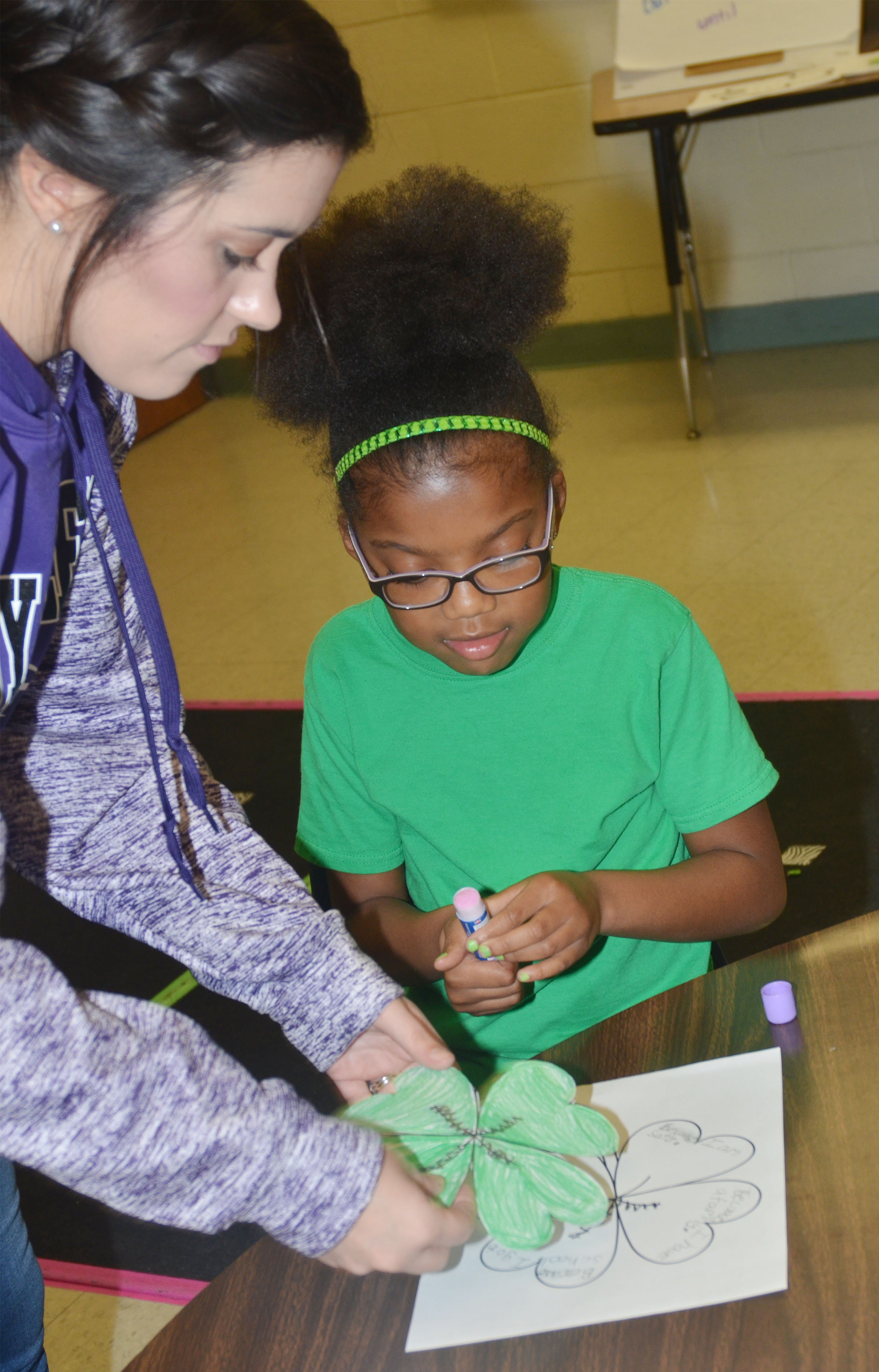 CES first-grade teacher Hailey Ogle helps Willow Griffin glue her shamrock to her worksheet, on which she wrote why she is lucky.
