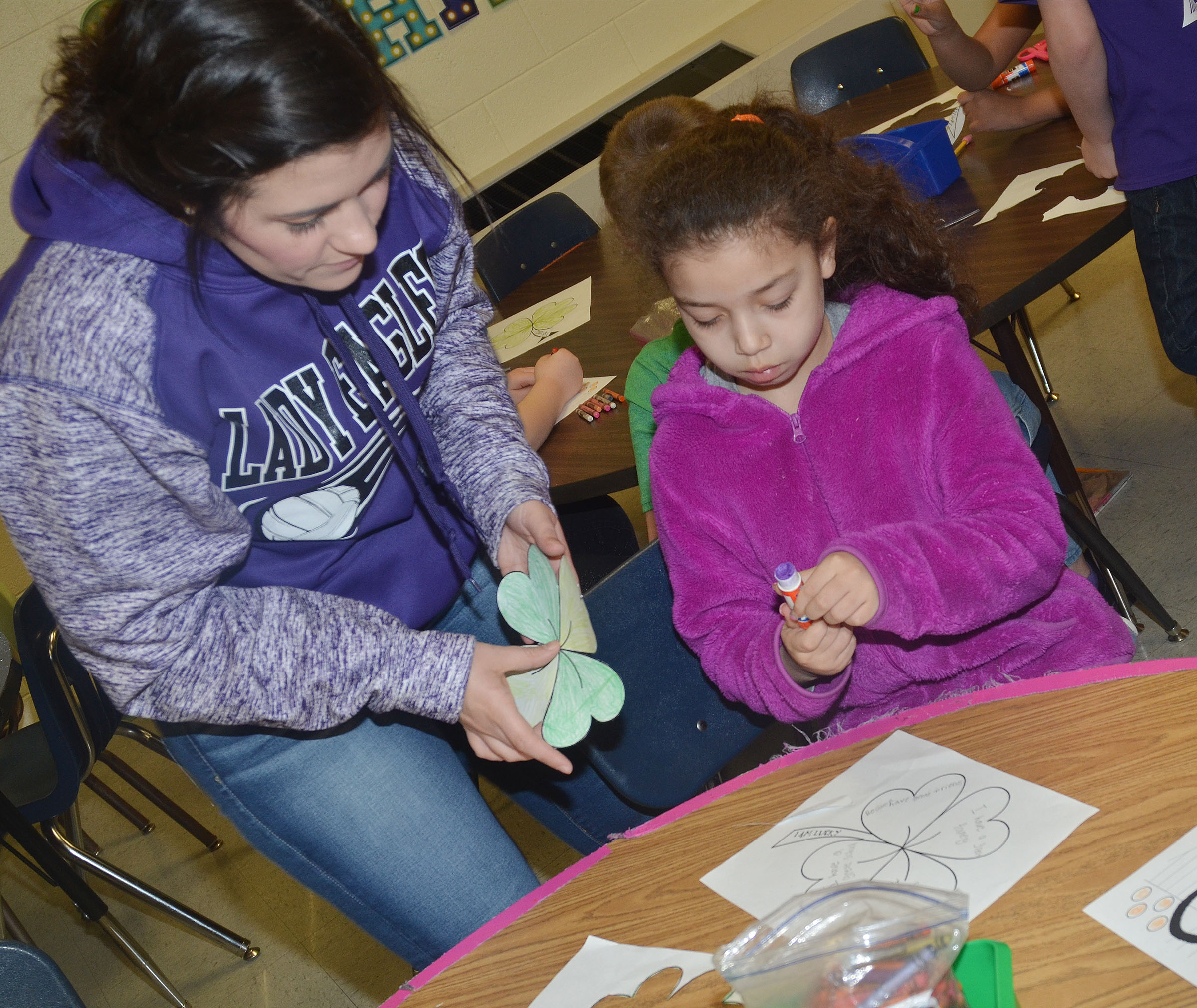 CES first-grade teacher Hailey Ogle helps Ammarissa Nunez glue her shamrock to her worksheet, on which she wrote why she is lucky.
