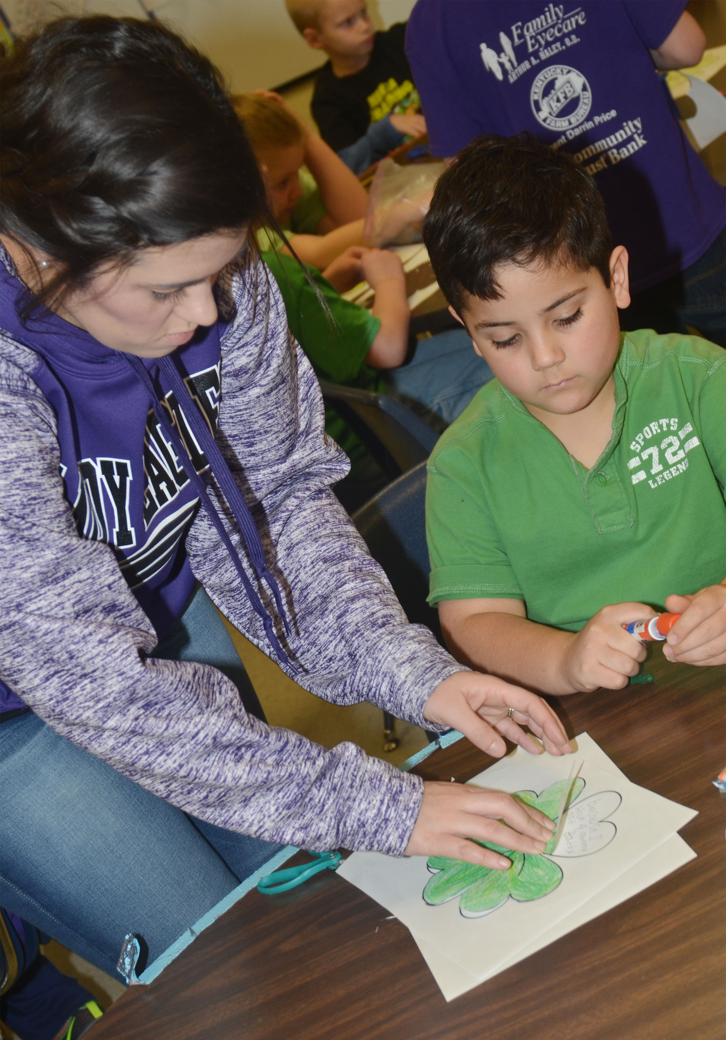 CES first-grade teacher Hailey Ogle helps Nicholas Almeida glue his shamrock to his worksheet, on which he wrote why he is lucky.
