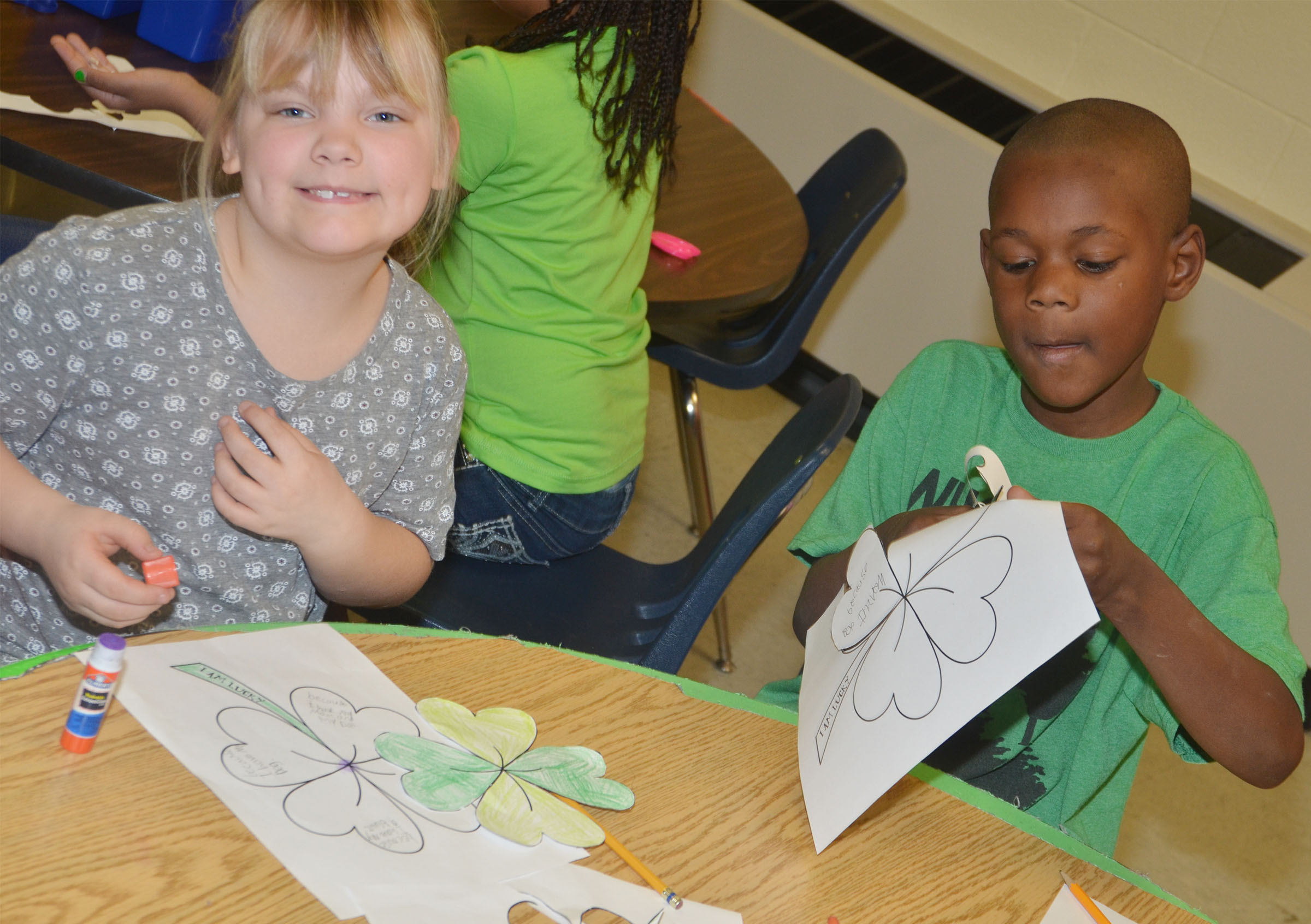 CES first-graders Addysen England, at left, and Lazarick Miller cut out and glue their shamrocks.