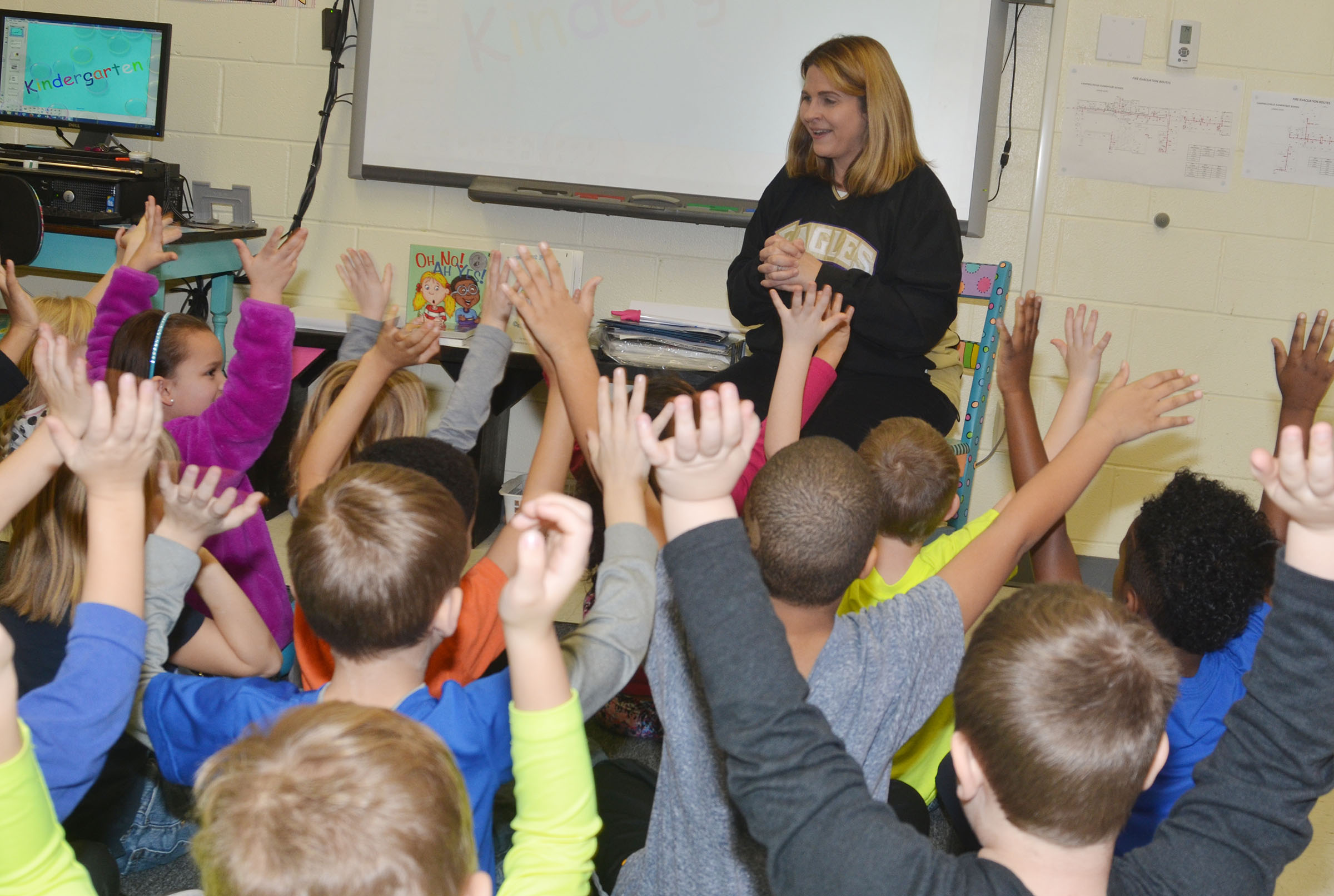 CES Guidance Counselor Sonya Orberson asks a question about how to act in an emergency and first-graders raise their hands to say they know the answer.
