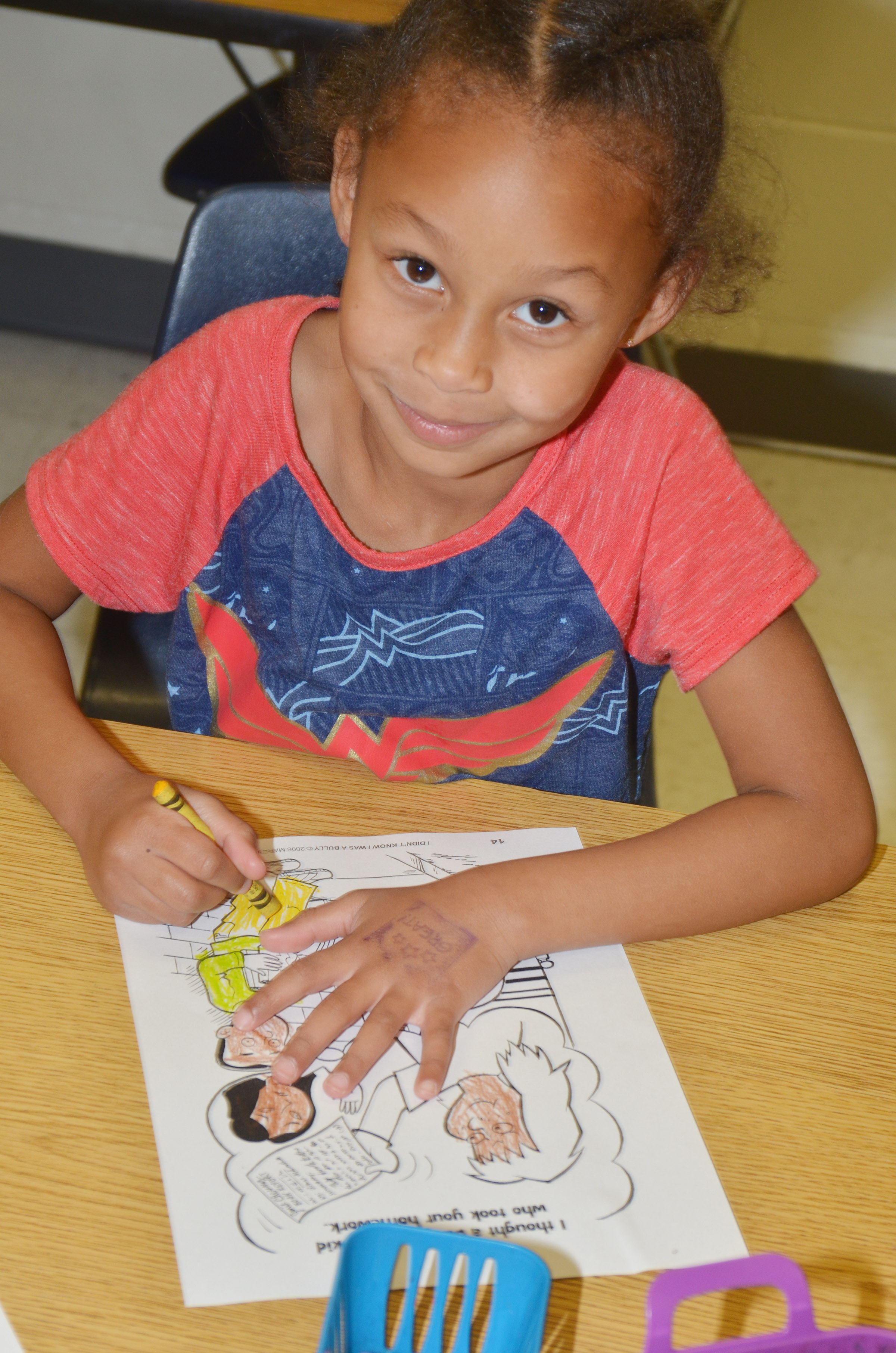 CES first-grader Elyzabeth Fisher colors her page of her class's bullying book.