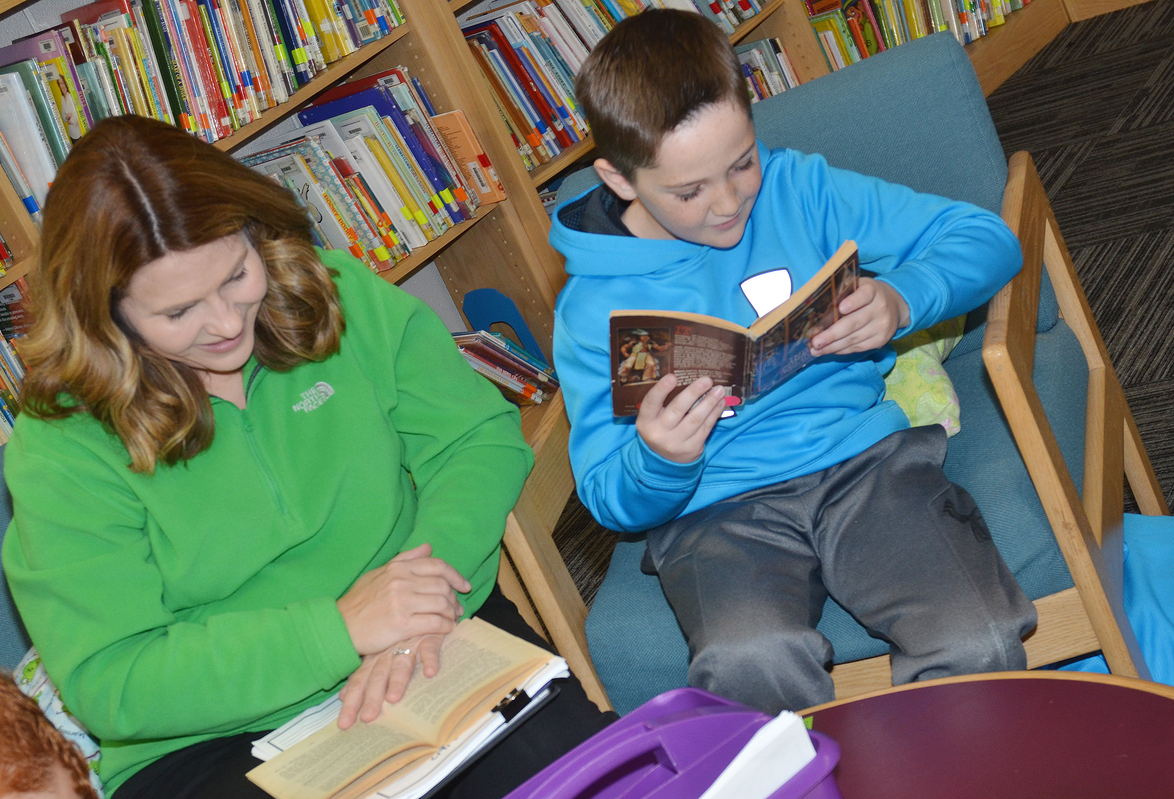 CES Guidance Counselor Sonya Orberson listens as third-grader Luke Adkins reads.