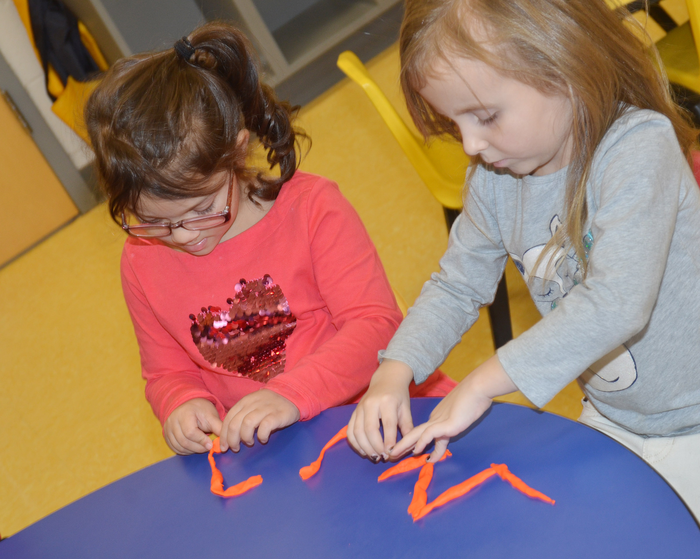 "CES preschool students Addisyn Taylor, at left, and Tabitha Leggett make the letter ""W"" with Play-Doh."