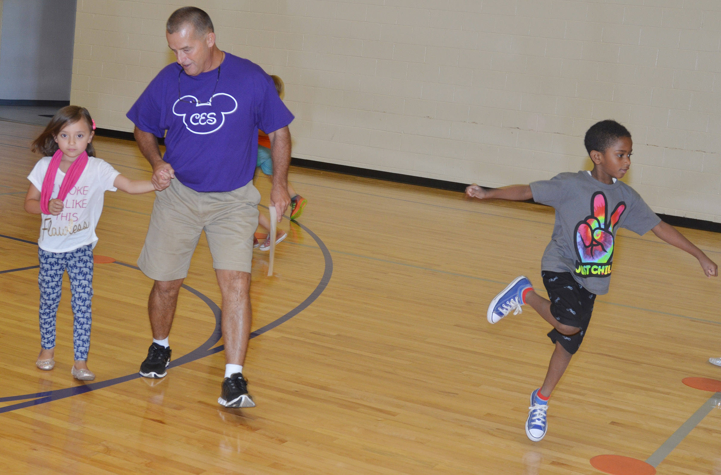 CES physical education teacher Lynn Kearney skips with first-grader Gabriella Tate.