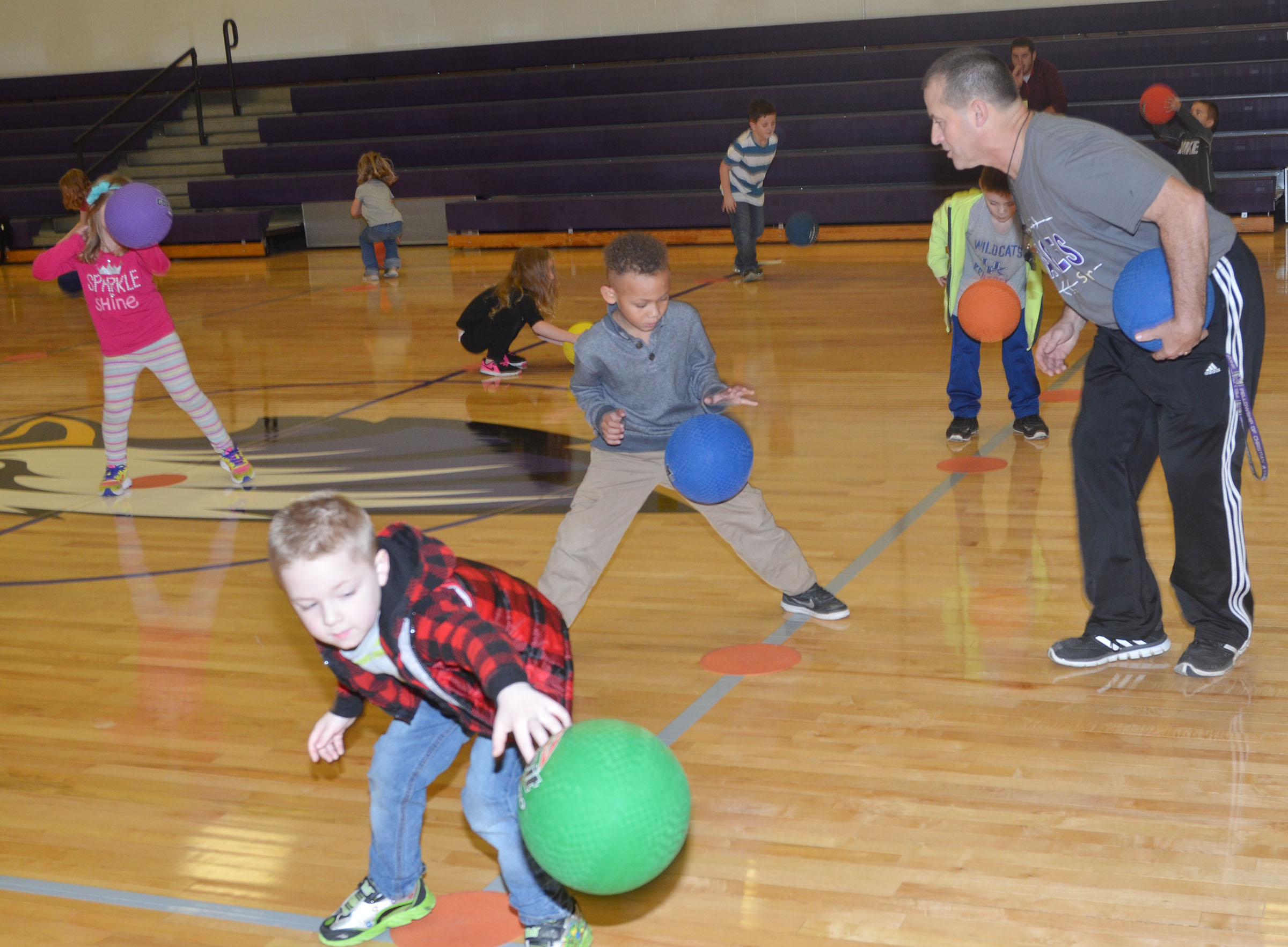 CES physical education teacher Lynn Kearney helps his students practice dribbling in the new CES gymnasium.