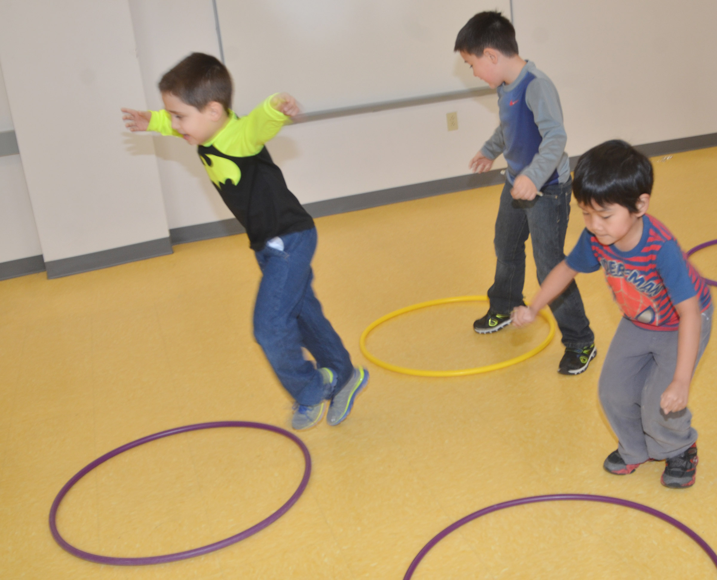 CES first-graders, from left, Aaron Floyd, Braxton Giles-Osinger and Zach Hak jump in their hula hoops.