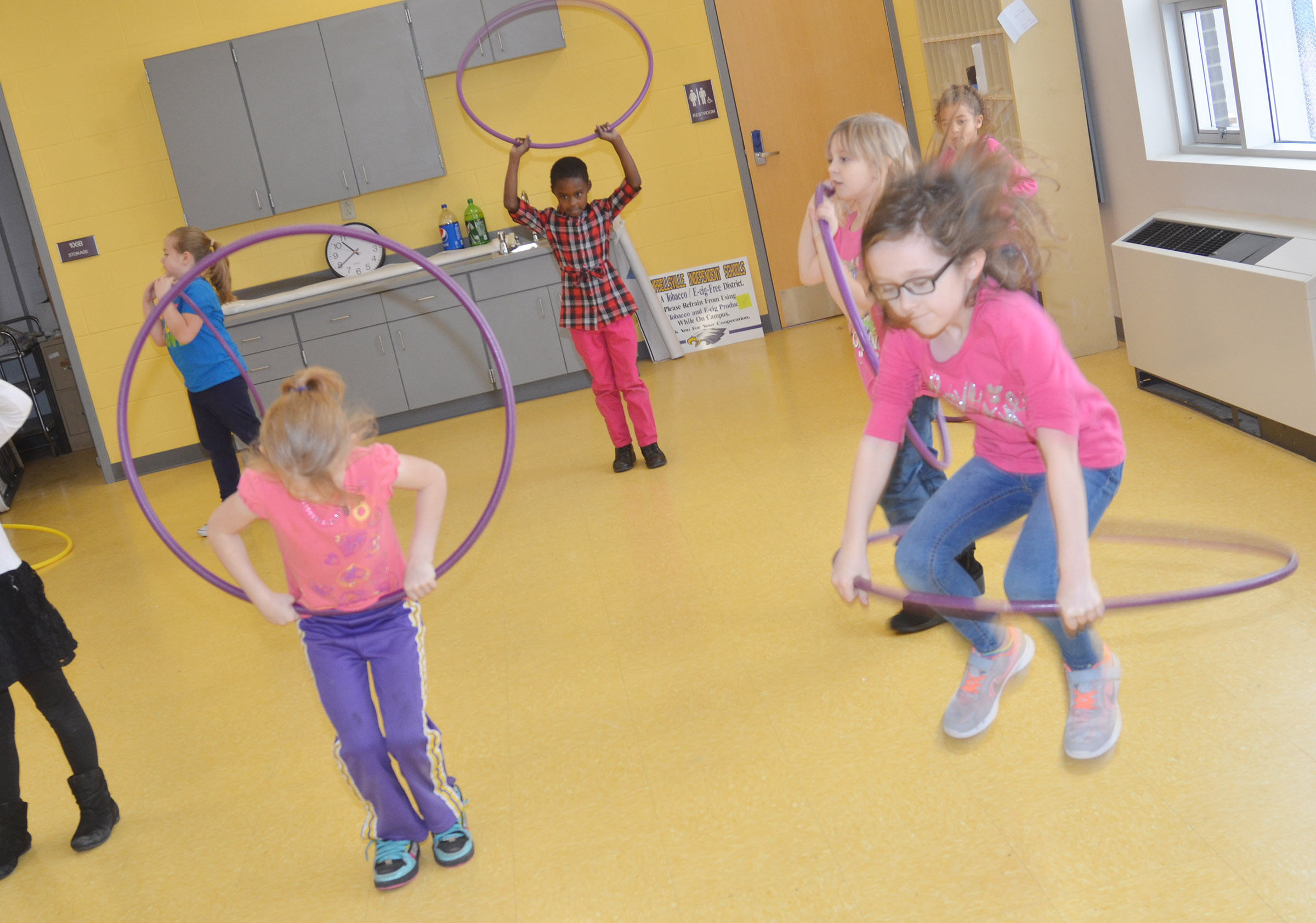 CES first-graders use their hula hoops as jump ropes.