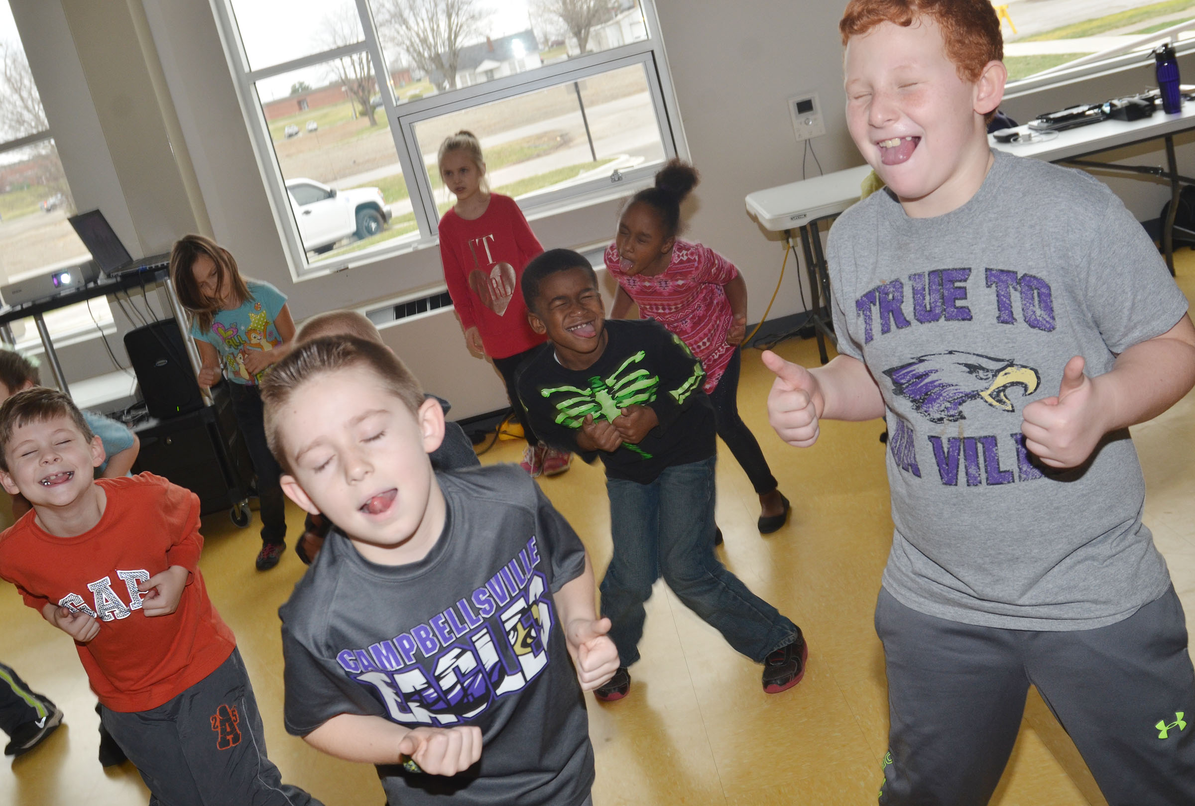 CES second-graders are instructed to close their eyes and stick out their tongues as they work out. In front are, from left, Ryan Tungate, Lanigan Price and Reece Swafford.