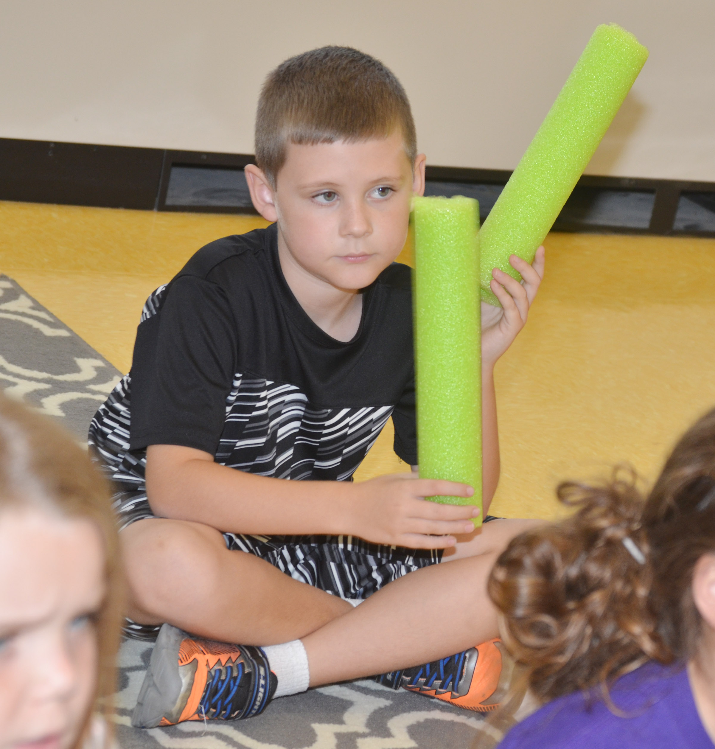 CES second-grader Ryan Tungate plays a rhythm with pool noodles.