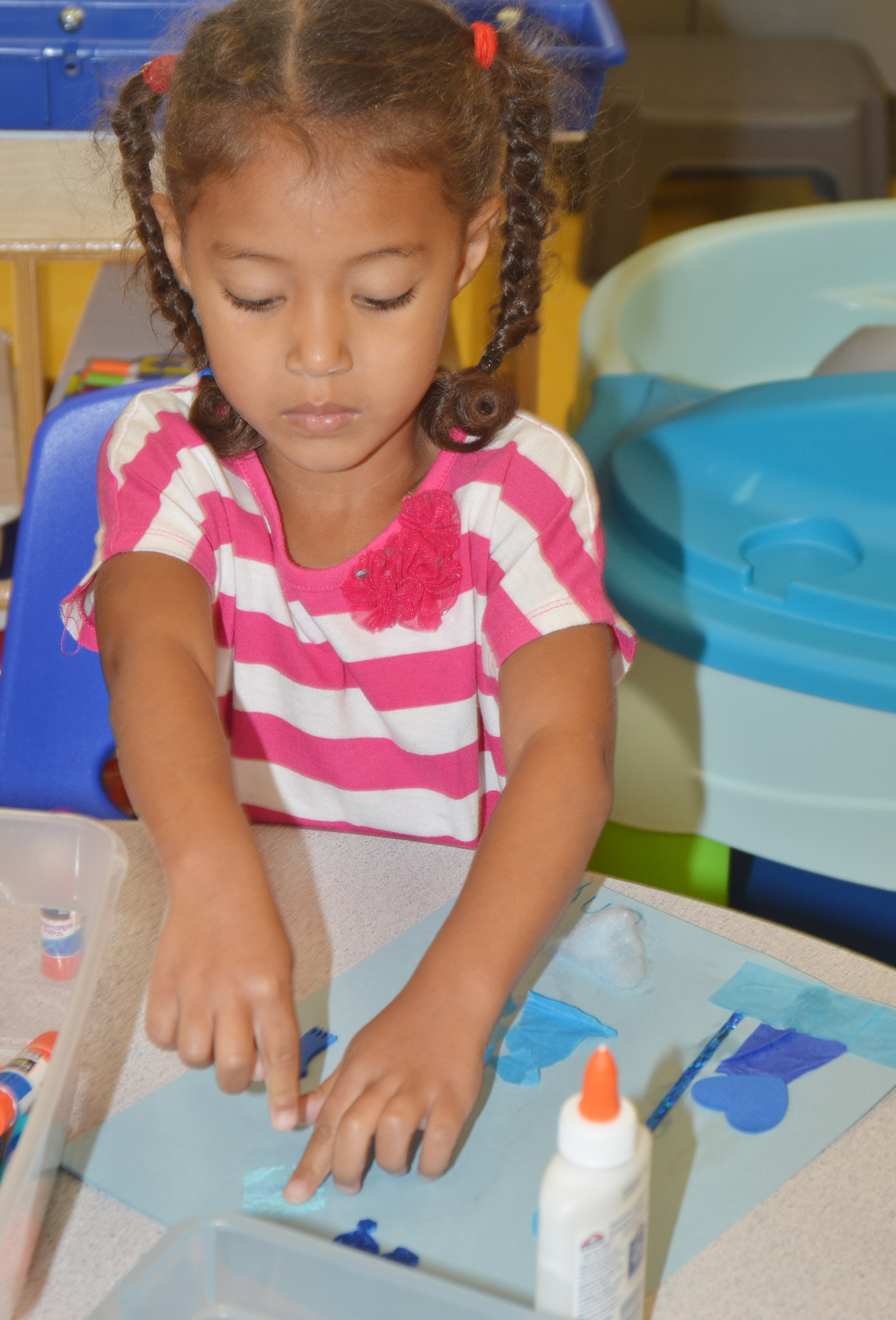 CES preschool student Onyx Hunter glues her blue collage.