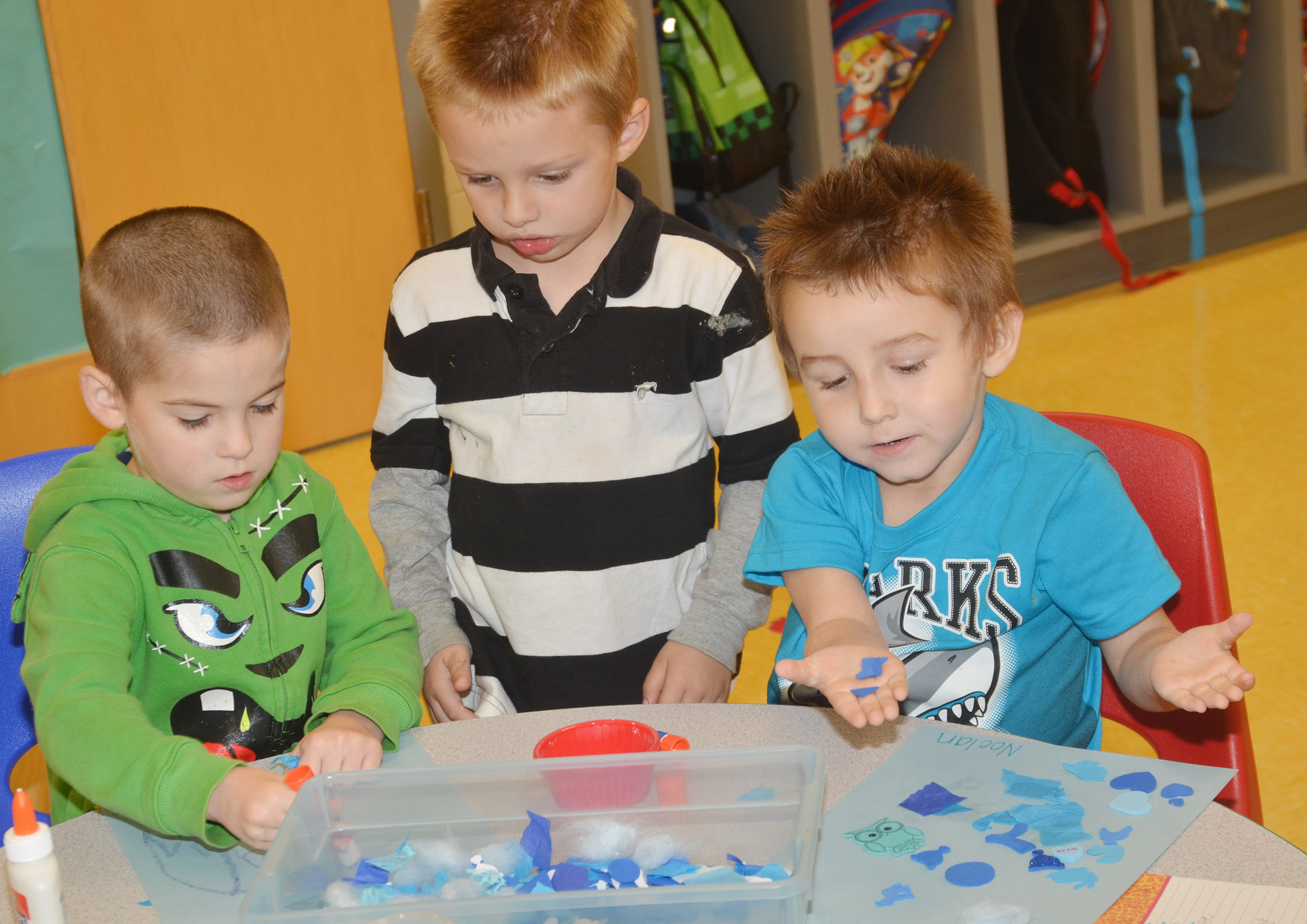 From left, CES preschool students Charlie Woodbury, Nevon Stum and Noelan McMahan work on their collages.