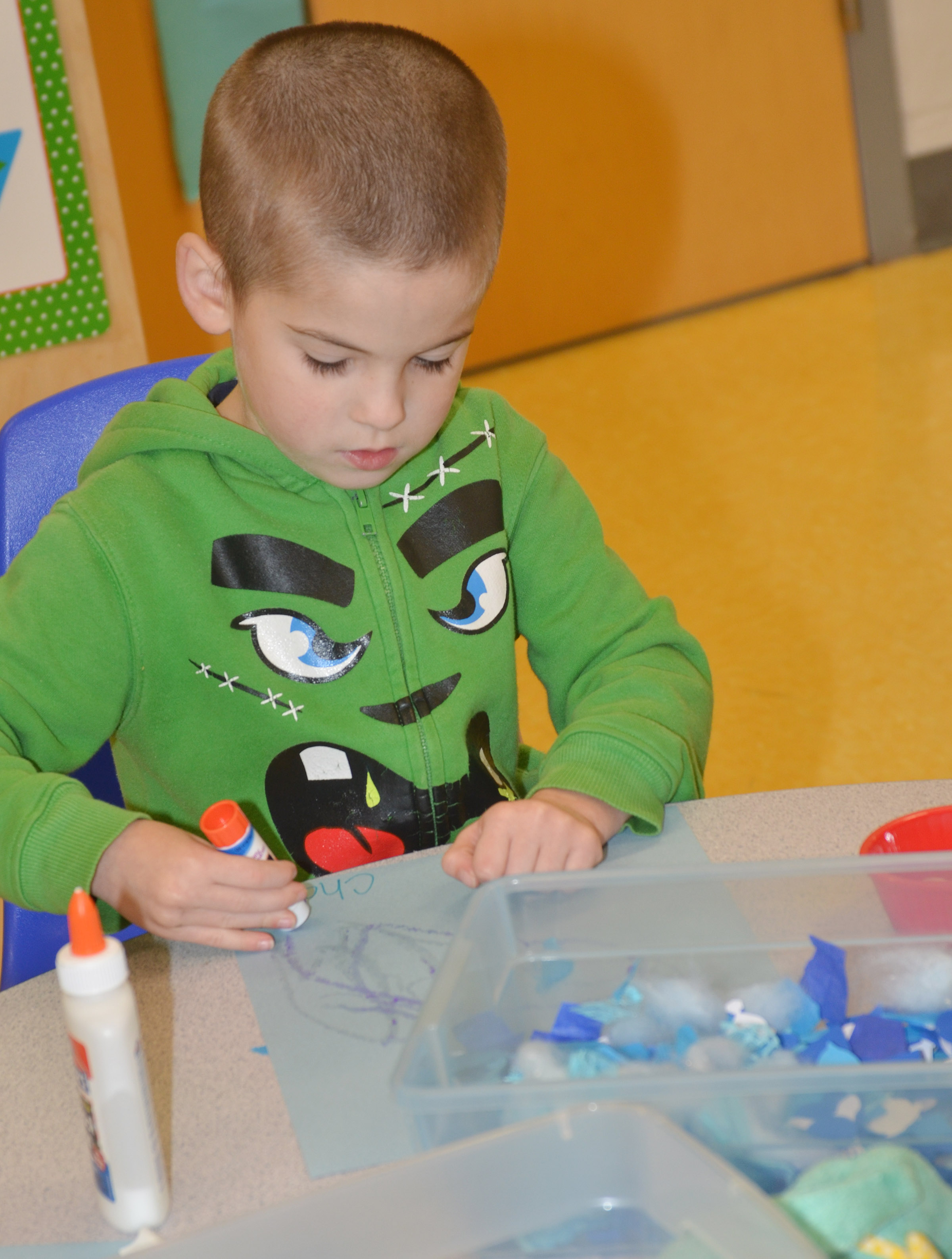 CES preschool student Charlie Woodbury glues his blue collage.